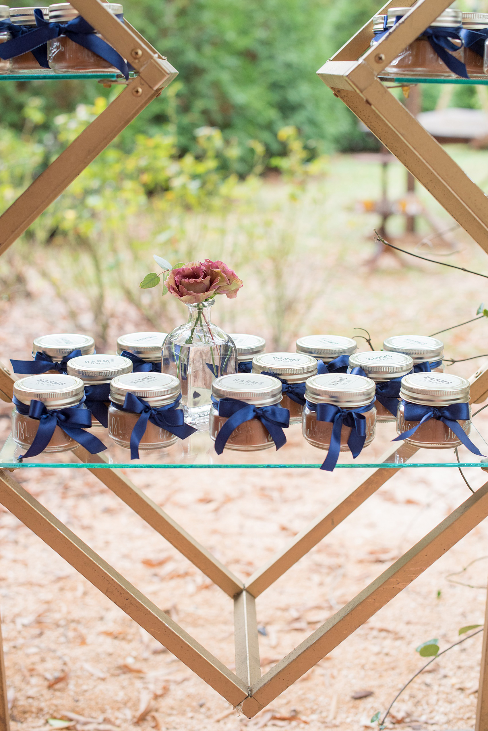 Mikkel Paige Photography photos from a wedding at Leslie-Alford Mims House in North Carolina. Picture of the gifts on a geometric metal display with blue ribbons and custom tags.