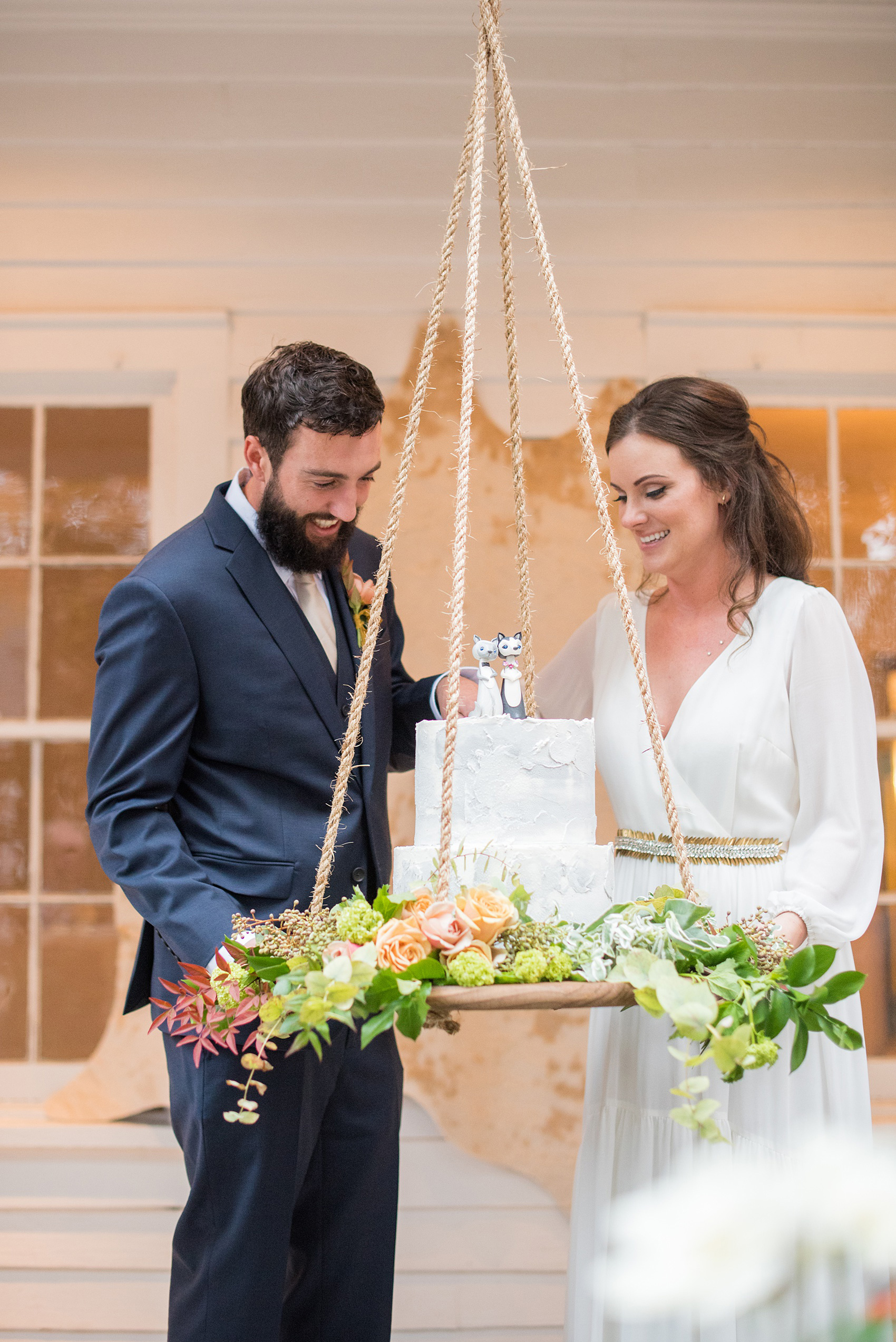 Mikkel Paige Photography photos from a wedding at Leslie-Alford Mims House in North Carolina. Picture of the bride and groom cutting their concrete cake with clay animal cake topper, suspended from the venue on a rope display adorned with flowers.