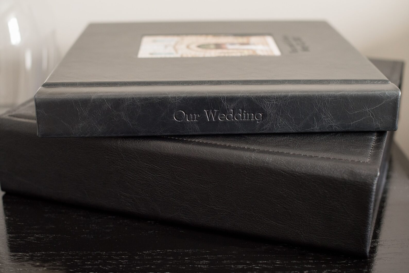 Images of a black calf leather fine art wedding album from Mikkel Paige Photography, a Raleigh, NC photographer. Photo shows spine debossing text.