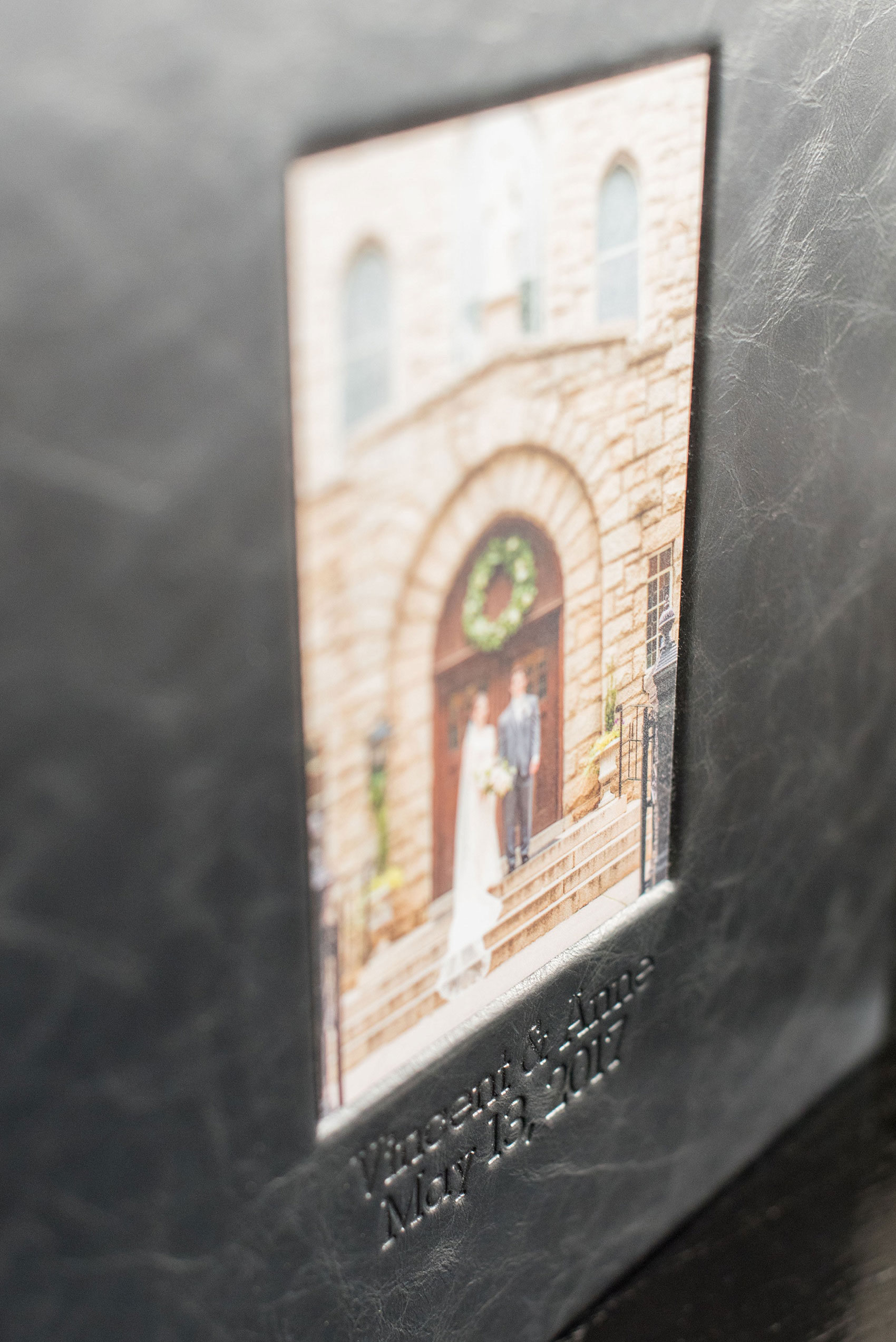 Images of a black calf leather fine art wedding album from Mikkel Paige Photography, a Raleigh, NC photographer. Photo shows inset cover image and debossing text.