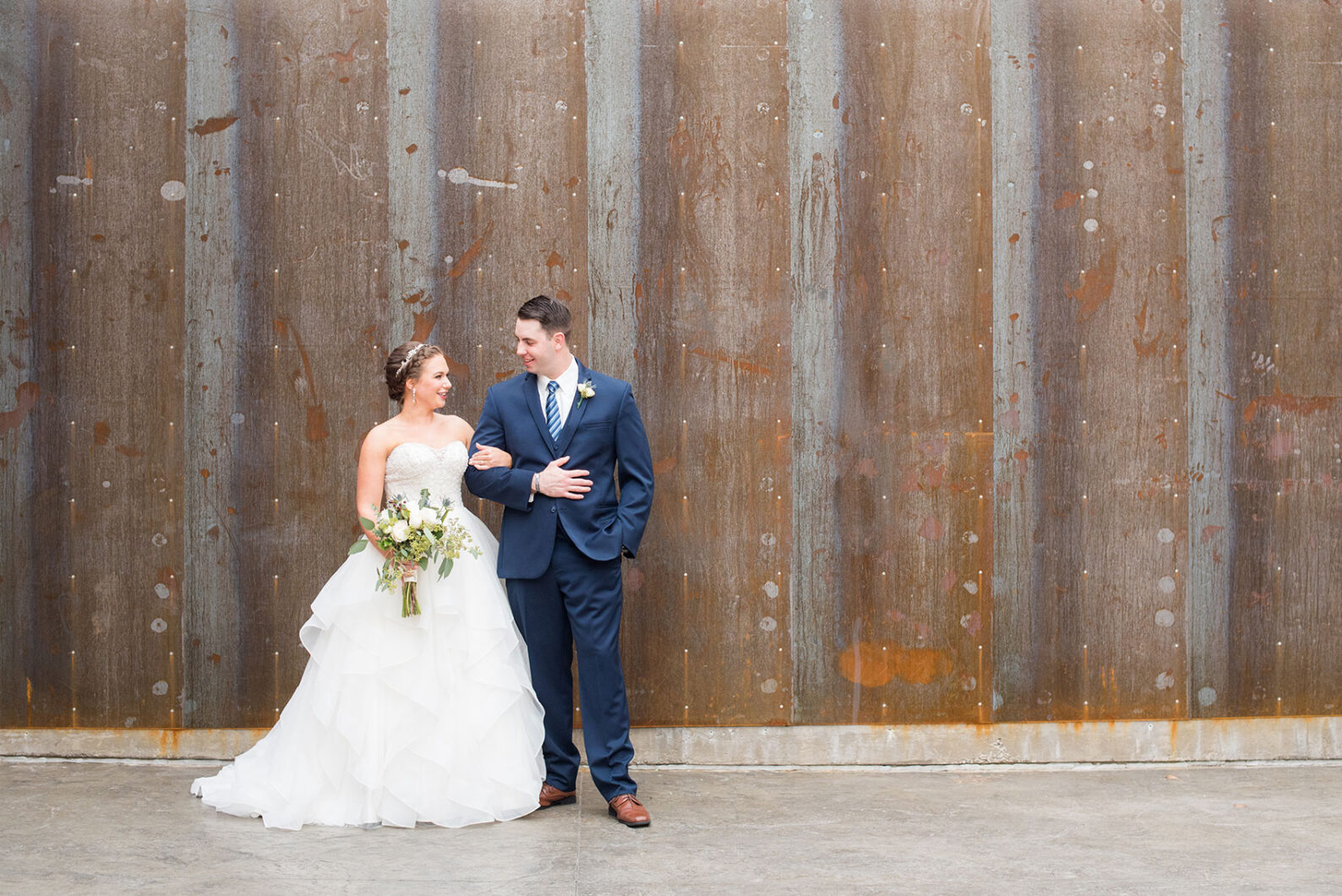 Durham wedding photos at The Cookery by Mikkel Paige Photography in North Carolina. The bride and the groom took pictures in front of a rustic, urban wall at the venue.