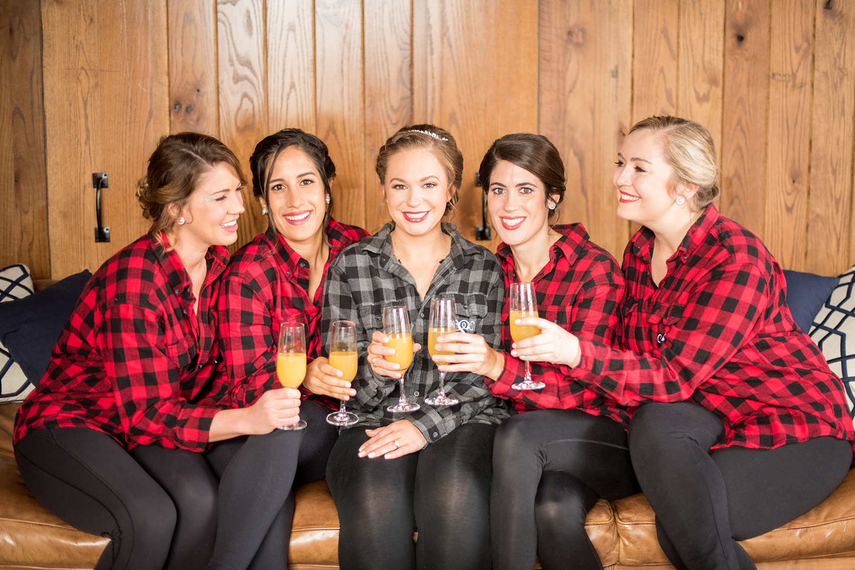 Durham wedding photos at The Cookery by Mikkel Paige Photography in North Carolina. The brought gifted her bridesmaids monogrammed button-down plaid shirts with their first initial on the pocket, as shown in this picture, for the getting ready and mimosa portion of the winter morning.