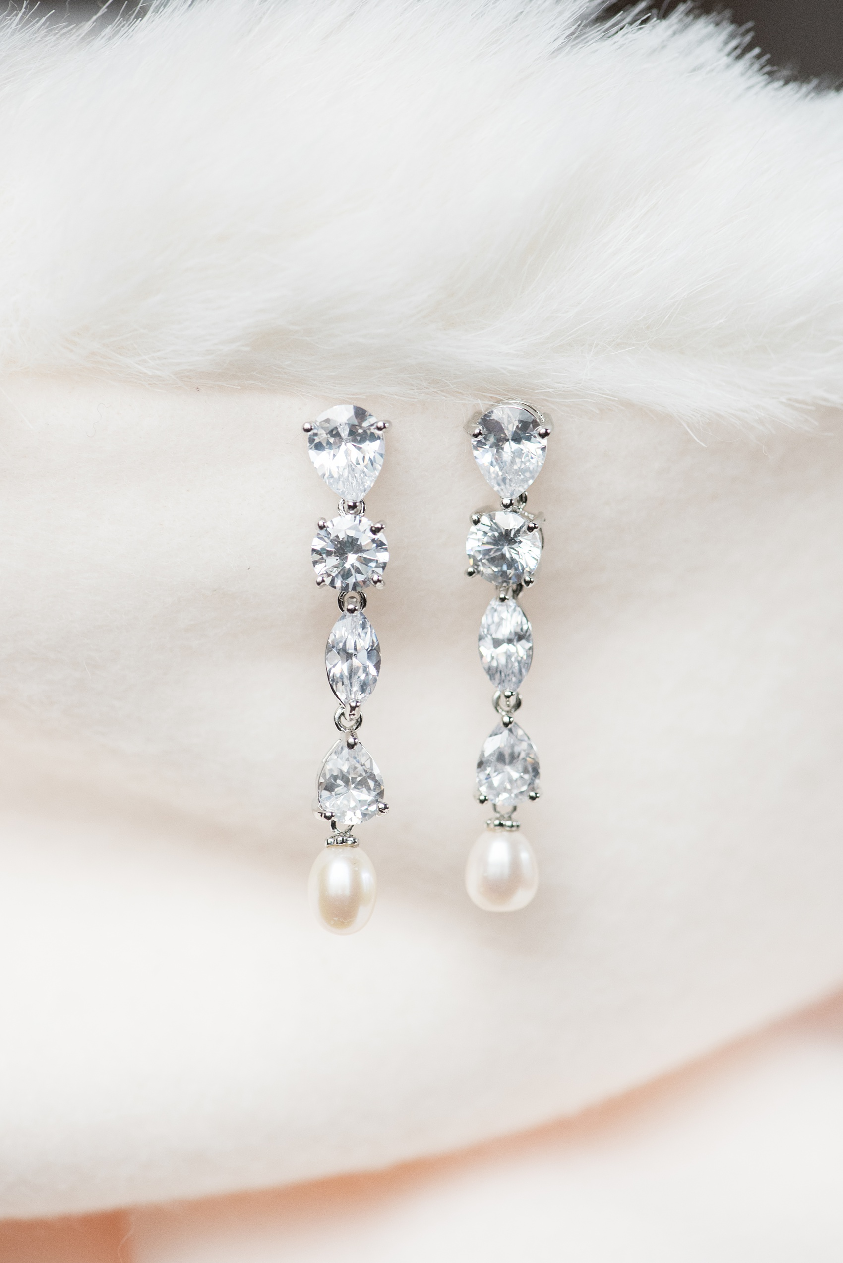 Durham wedding photos at The Cookery by Mikkel Paige Photography in North Carolina. This detail picture shows the bride's diamond and pearl hanging earrings.