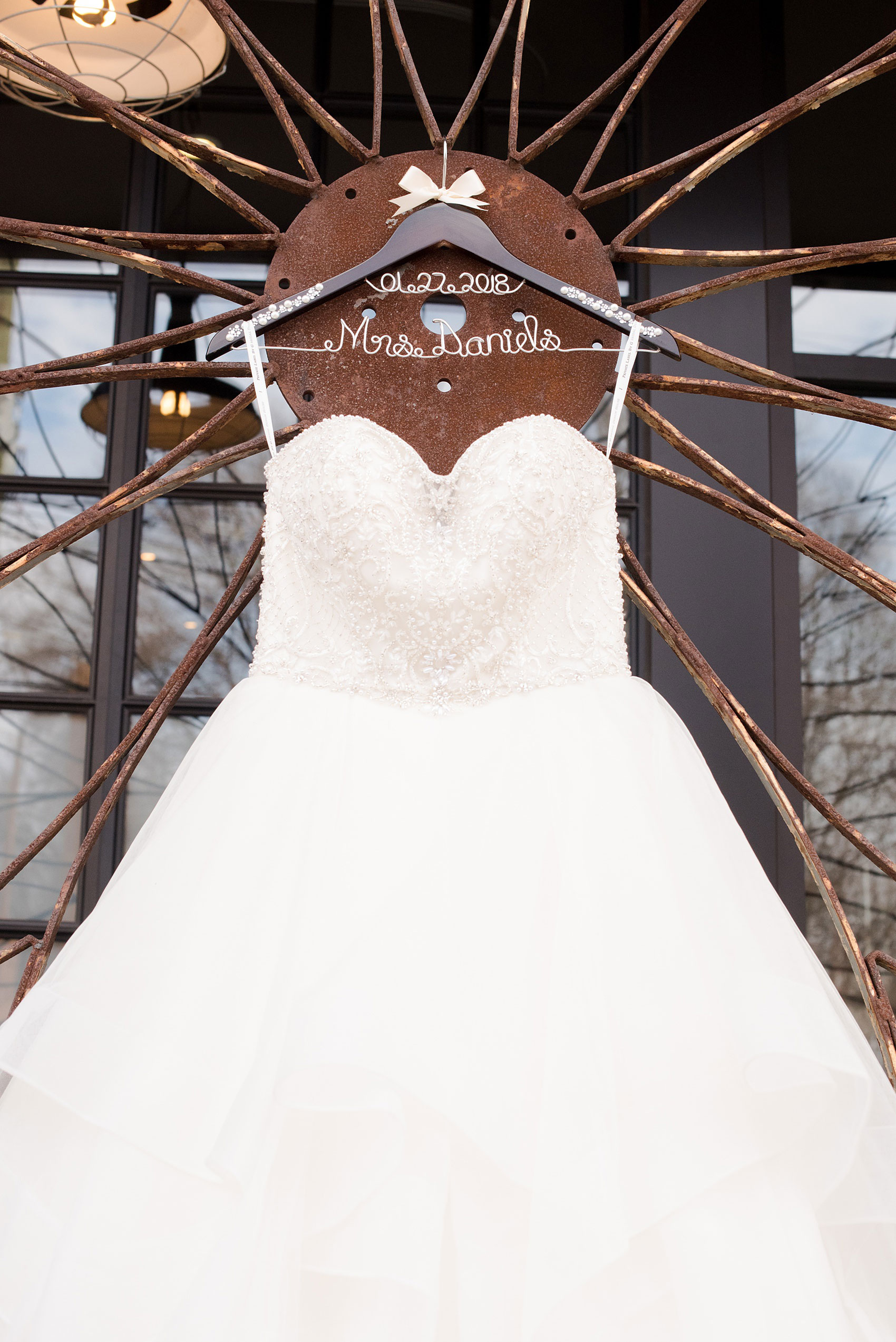 Durham wedding photos at The Cookery by Mikkel Paige Photography in North Carolina. The bride wore a strapless beaded gown, shown in a detailed picture on a rustic front gate at the venue, on a special pearl and rhinestone hanger.