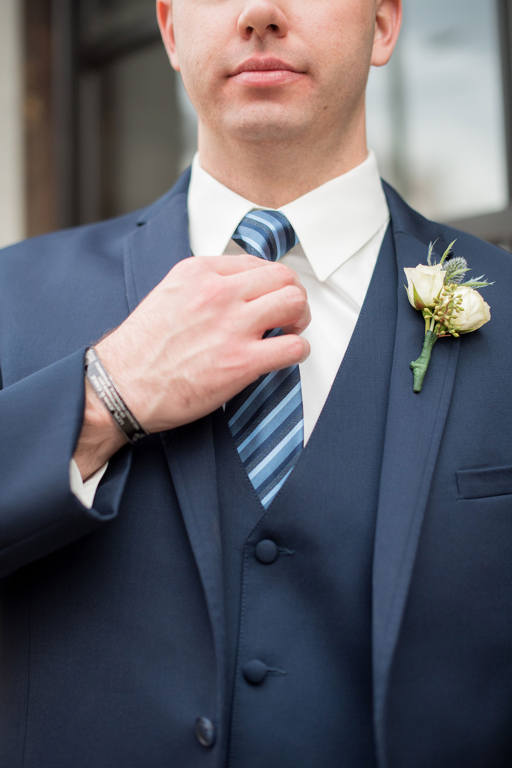 Durham wedding photos at The Cookery by Mikkel Paige Photography in North Carolina. The groom wore a navy double-breasted blue suit with a striped tie and white boutonniere.