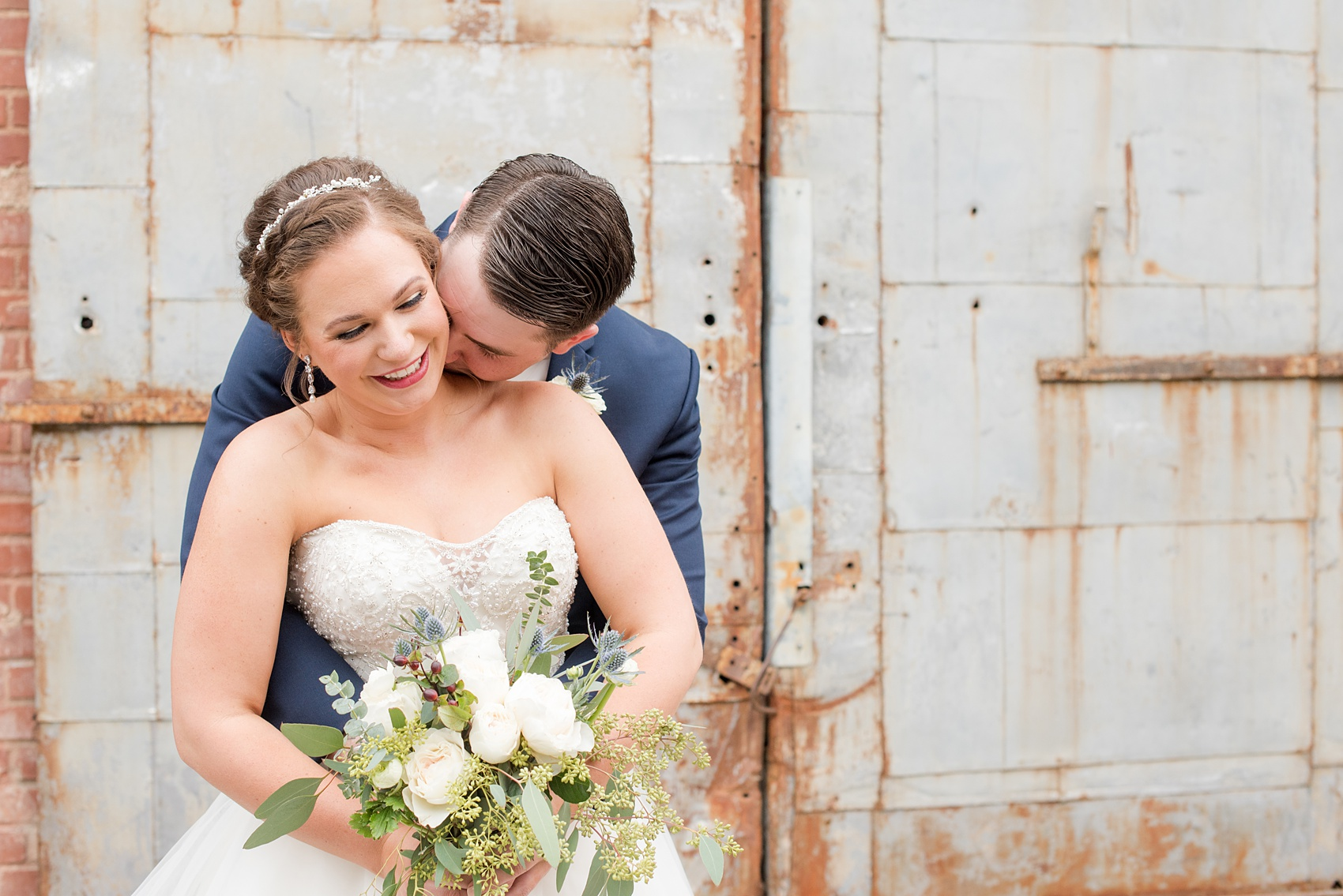 Durham wedding photos at The Cookery by Mikkel Paige Photography in North Carolina. In this cute picture of the bride and groom he kisses her neck in front of the venue's rustic metal door.