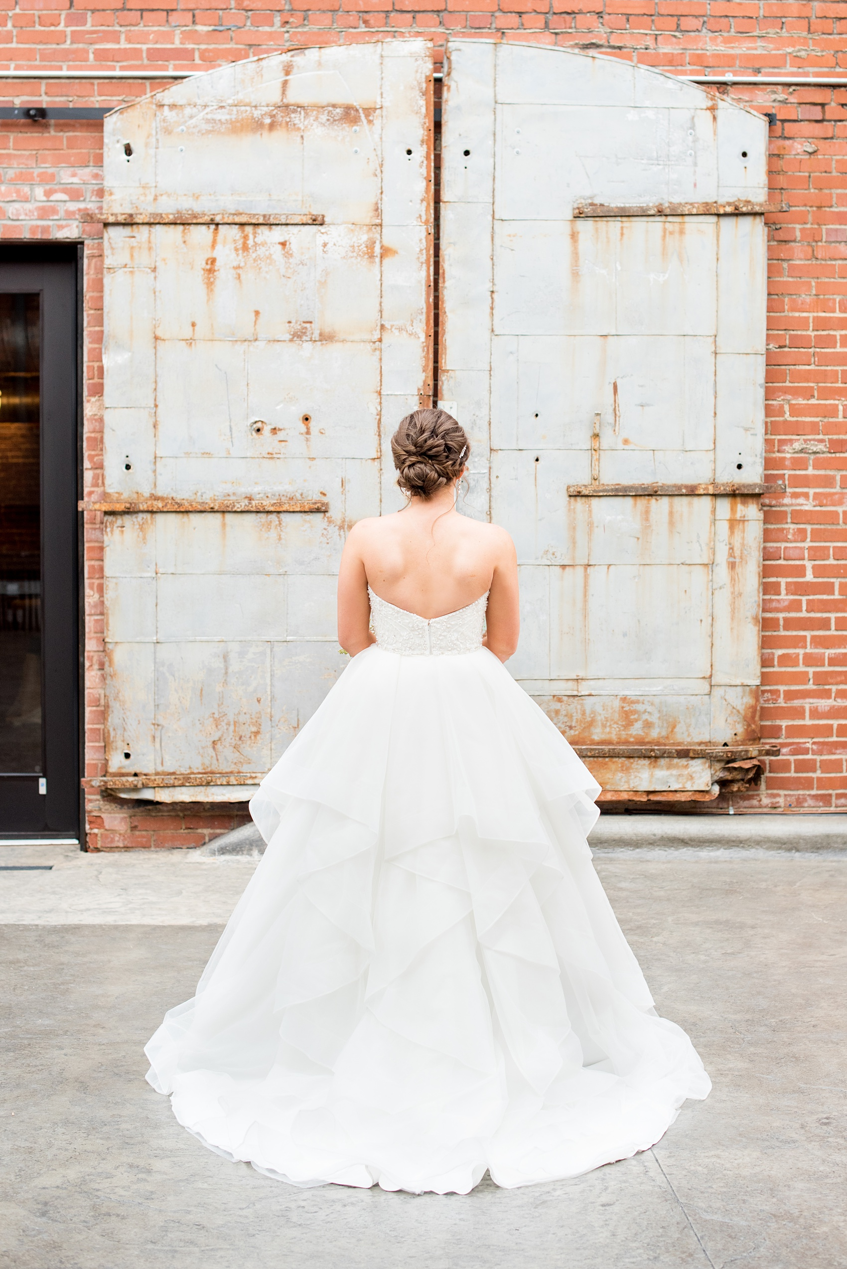 Durham wedding photos at The Cookery by Mikkel Paige Photography in North Carolina. The bride wore a strapless gown, had her hair in an up-do, and had many layers in her tulle skirt.