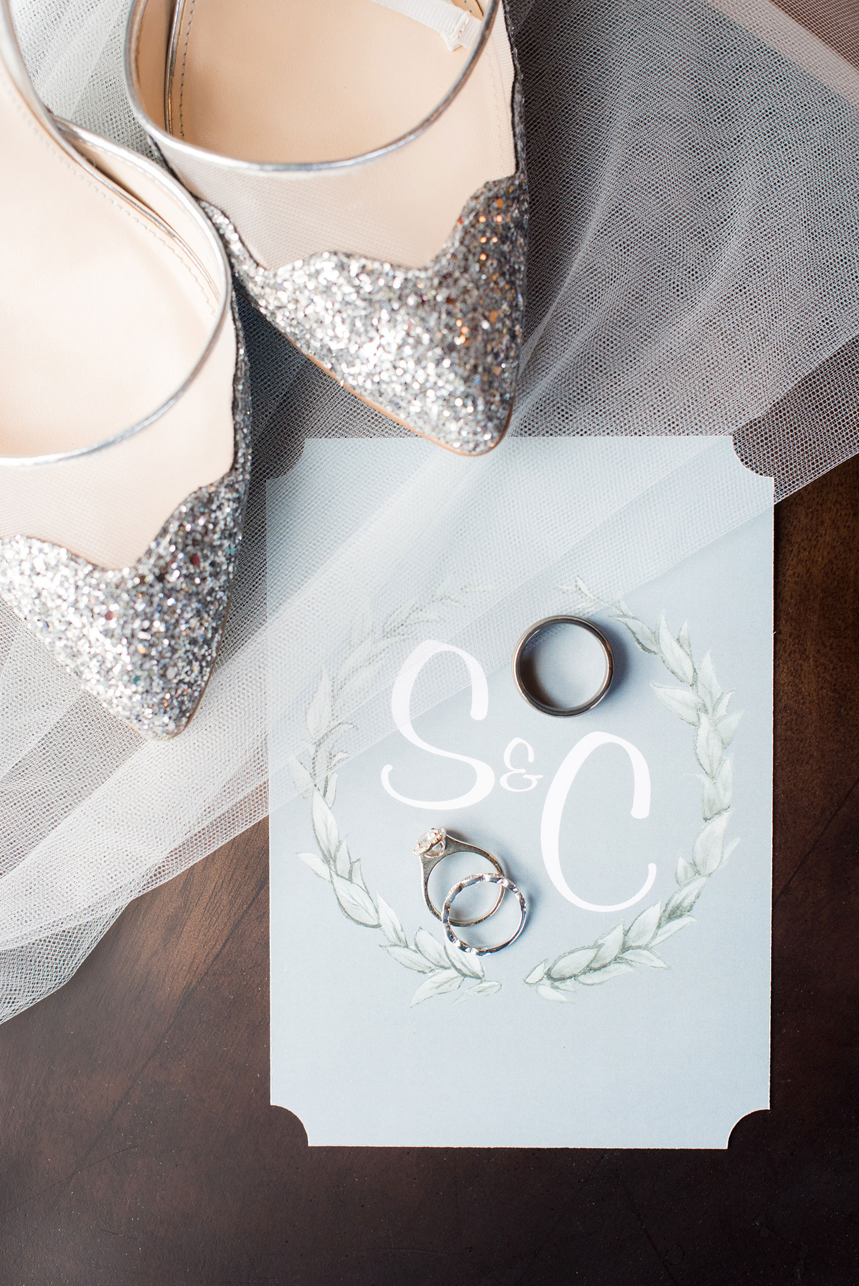 Durham wedding photos at The Cookery by Mikkel Paige Photography in North Carolina. The bride's glitter shoes, couple's rings and monogrammed back of their winter invitation are styled in this detail photo.