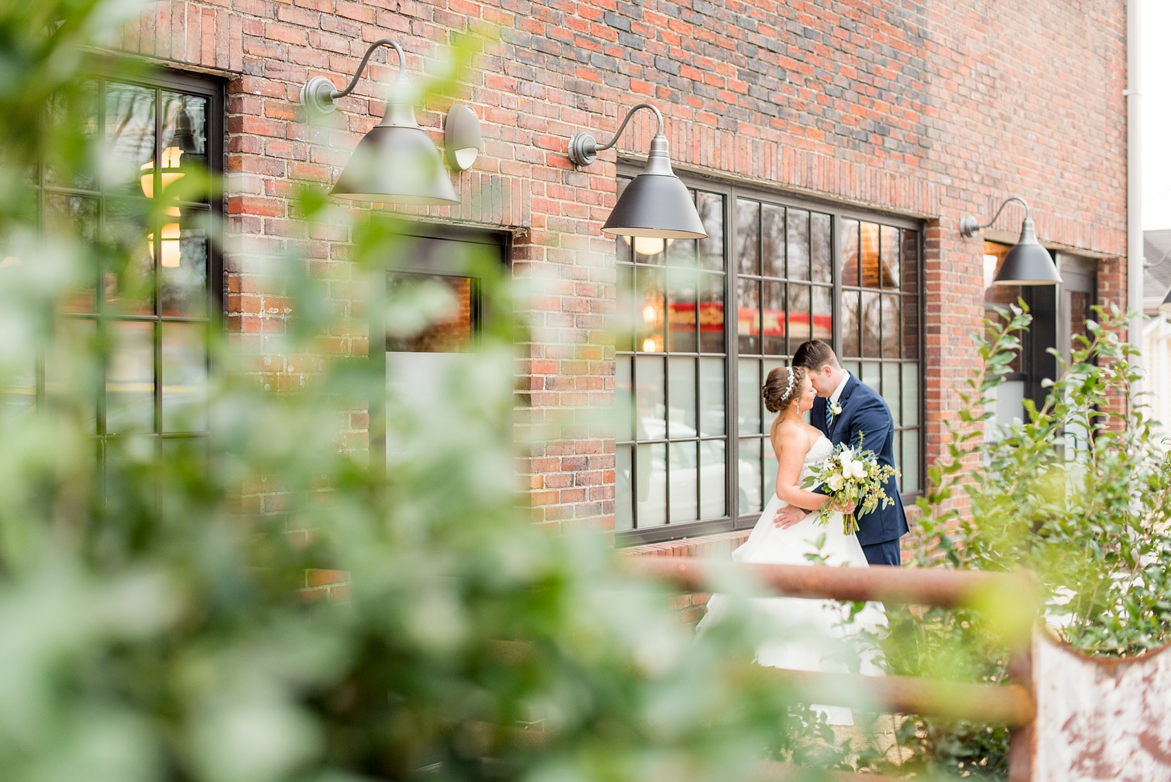 Durham wedding photos at The Cookery by Mikkel Paige Photography in North Carolina. The bride and groom stole a kiss in front of their brick, urban venue during their winter day.
