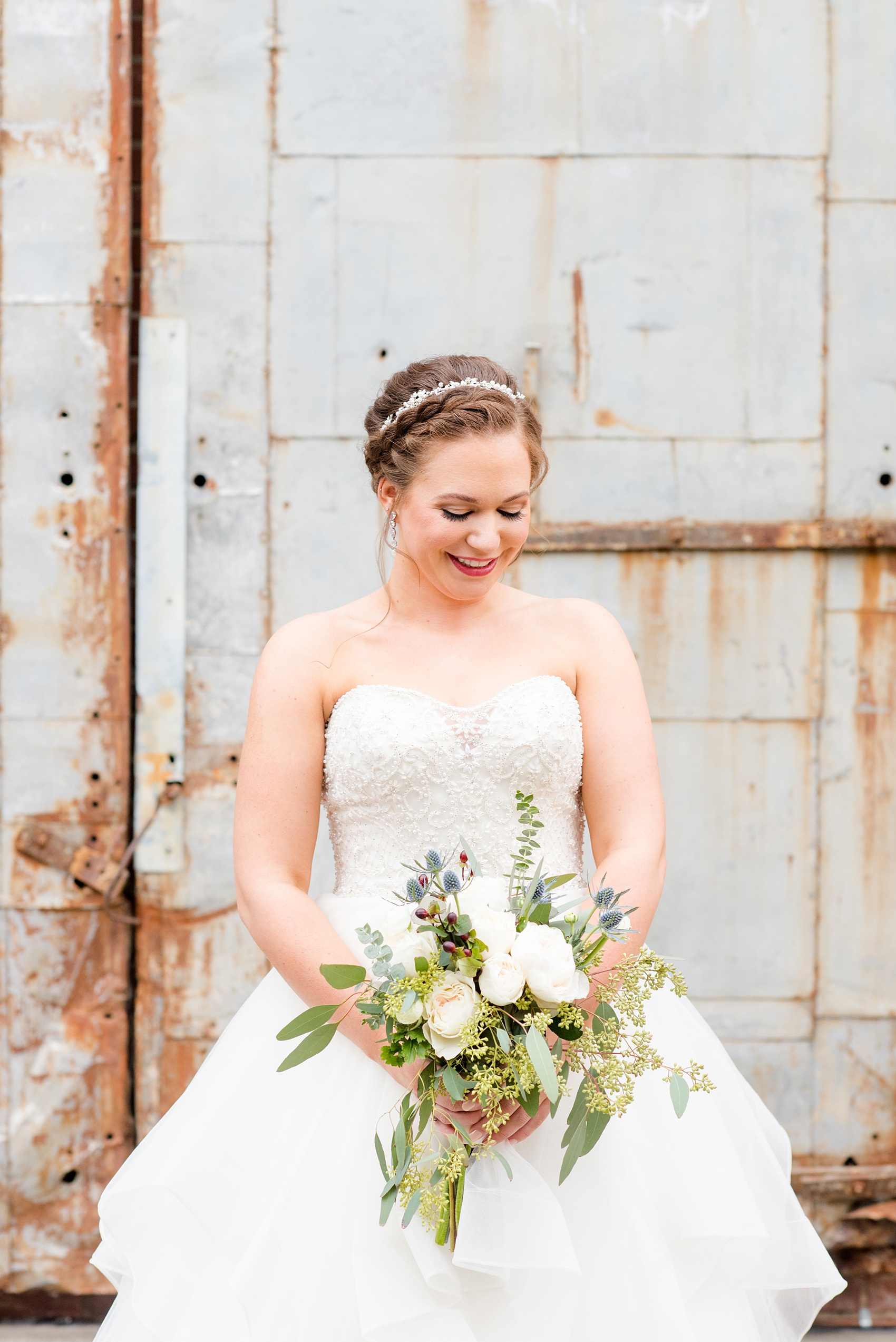 Durham wedding photos at The Cookery by Mikkel Paige Photography in North Carolina. The bride wore a strapless beaded gown, braided up-do and held a bouquet of roses, blue thistle and eucalyptus for her winter day. In this picture she's posing in front of the venue's rustic doors.