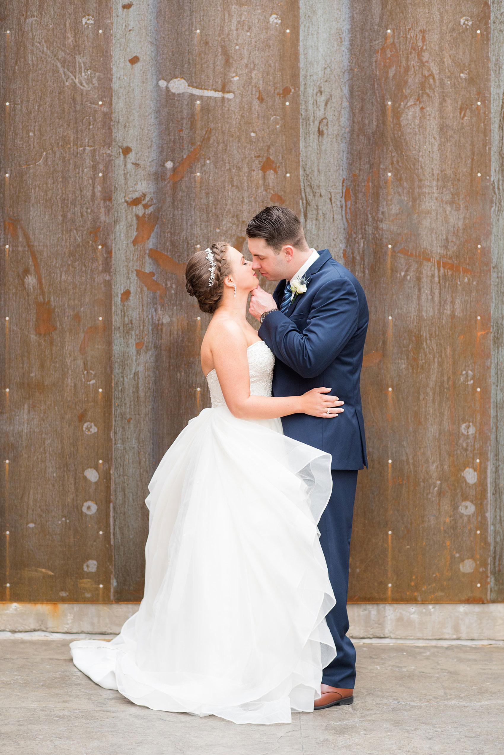 Durham wedding photos at The Cookery by Mikkel Paige Photography in North Carolina. The bride wore a strapless beaded gown with many layers in the skirt and groom wore a navy blue suit at their rustic winter day.