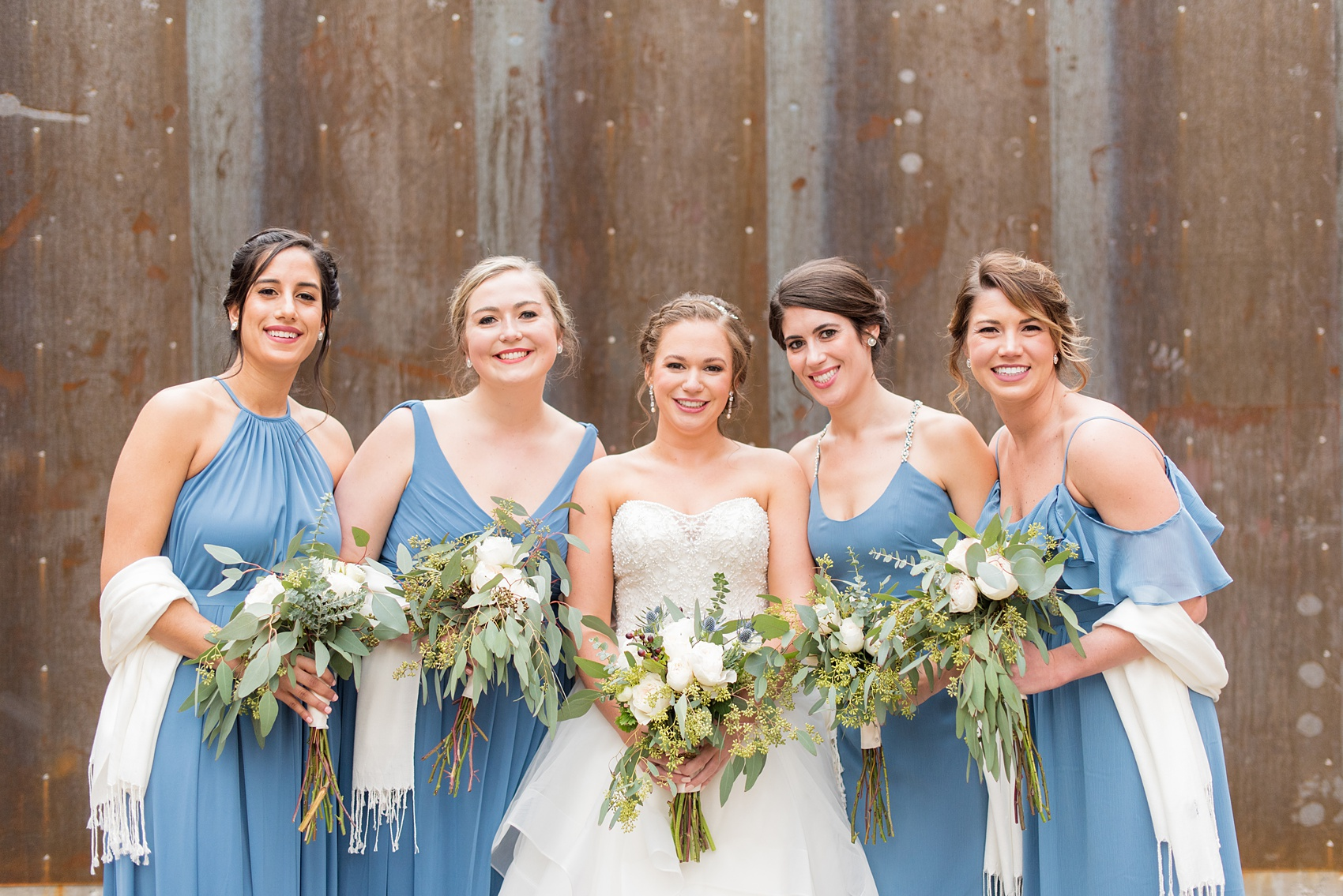 Bridesmaids Durham wedding photos at The Cookery by Mikkel Paige Photography in North Carolina. The bridal party wore different blue dresses, had white shawls for the winter wedding, and stood by the bride for this urban picture.