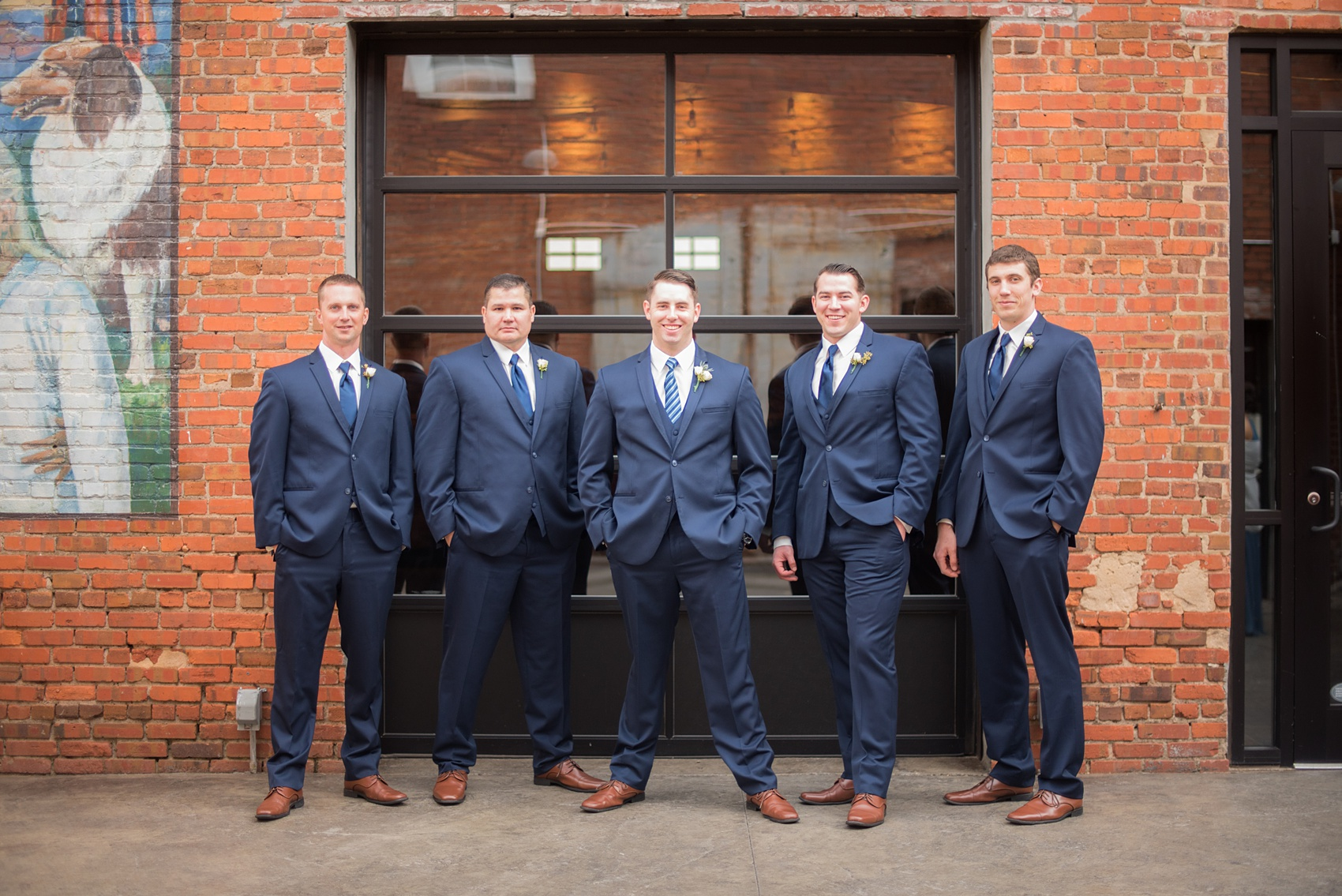 Durham wedding photos at The Cookery by Mikkel Paige Photography in North Carolina. The groomsmen wore navy blue suits with ties and brown shoes, posing for a picture in front of the brick urban outside of the venue.