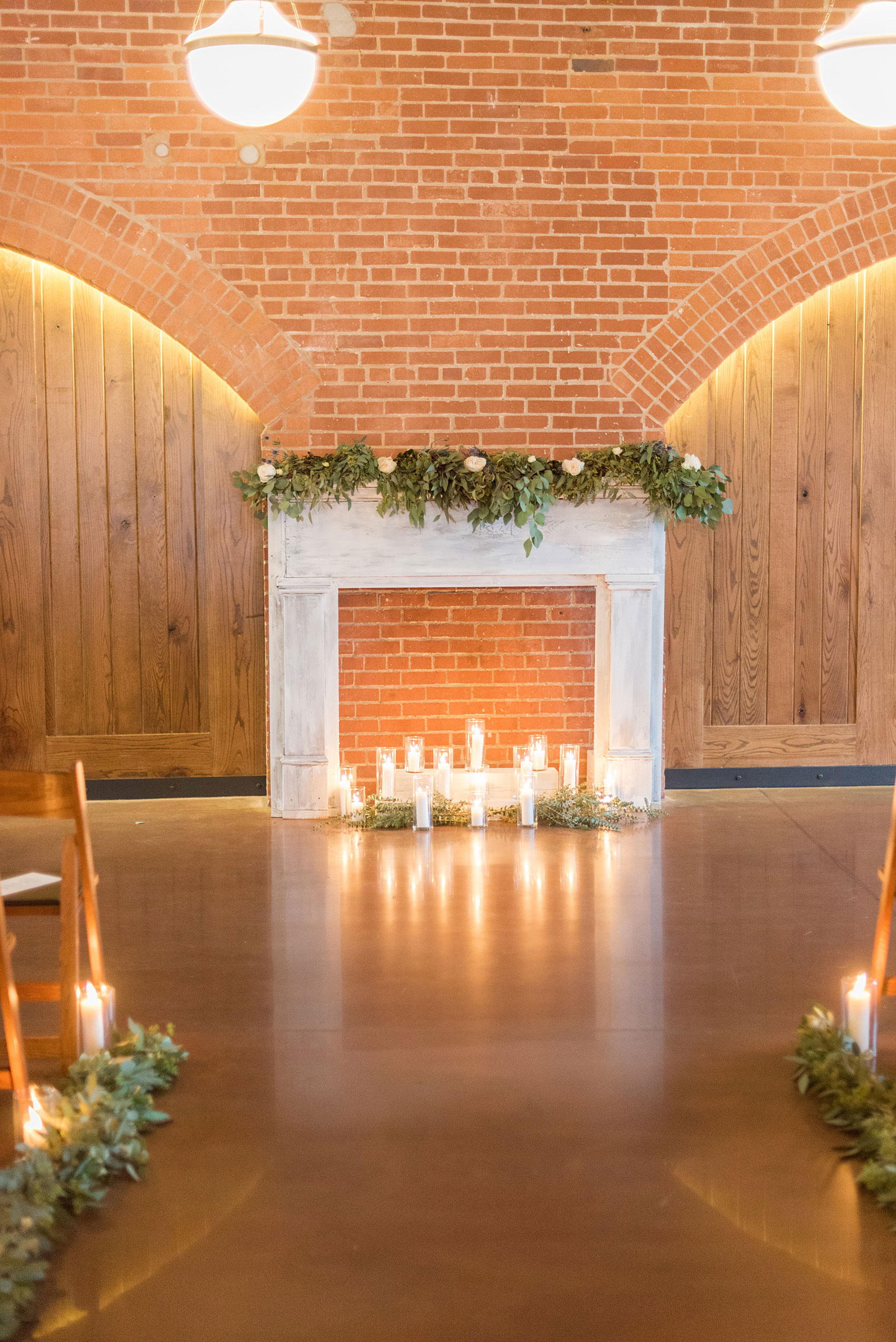 Durham wedding photos at The Cookery by Mikkel Paige Photography in North Carolina. The bride's father created a faux fireplace, decorated with lots of candlelight and green garland and white roses. It served as the indoor ceremony backdrop and eucalyptus lined the aisle.