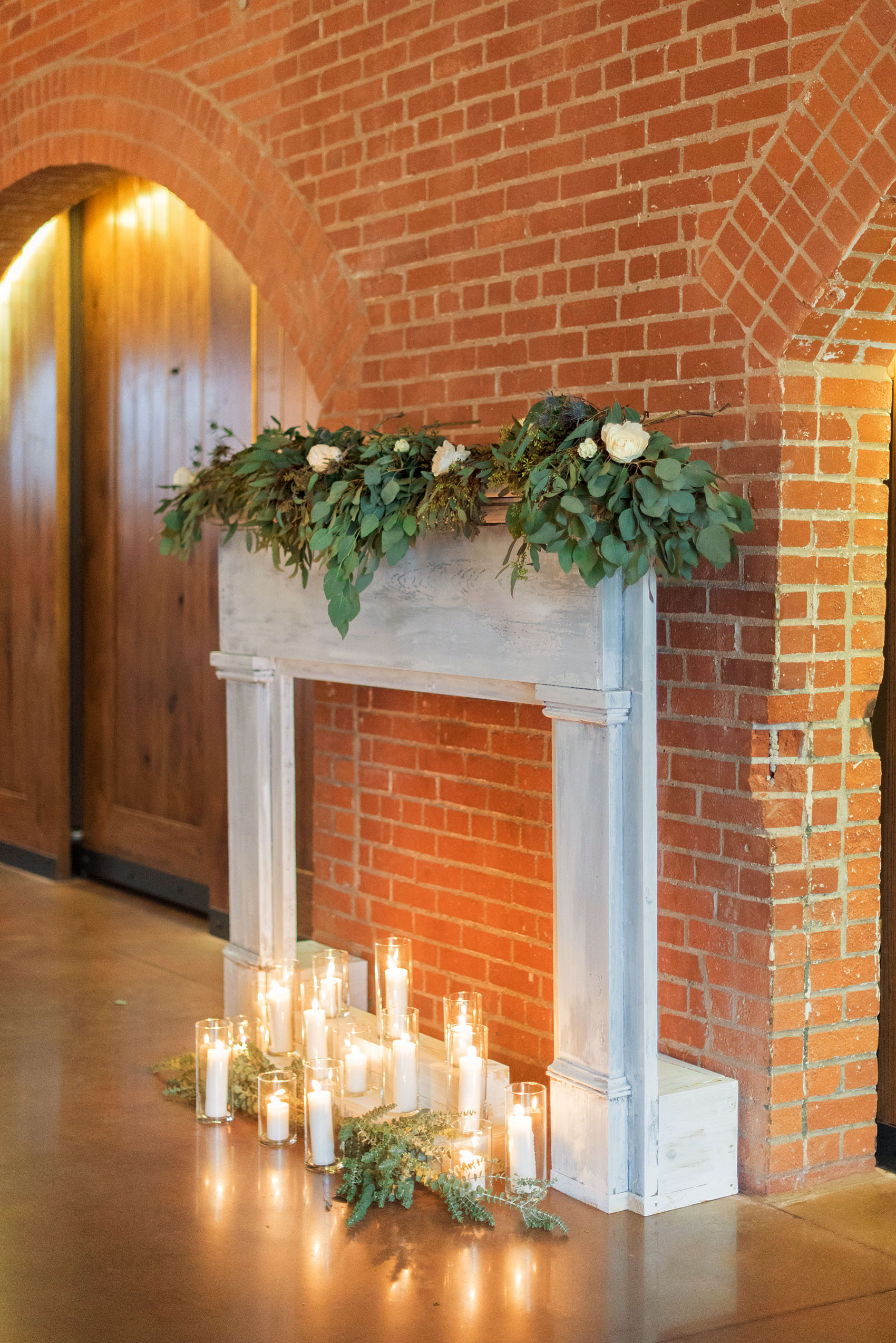 Durham wedding photos at The Cookery by Mikkel Paige Photography in North Carolina. The bride's father created this faux fireplace, decorated with lots of candlelight and green garland and white roses. It also served as the indoor ceremony backdrop.