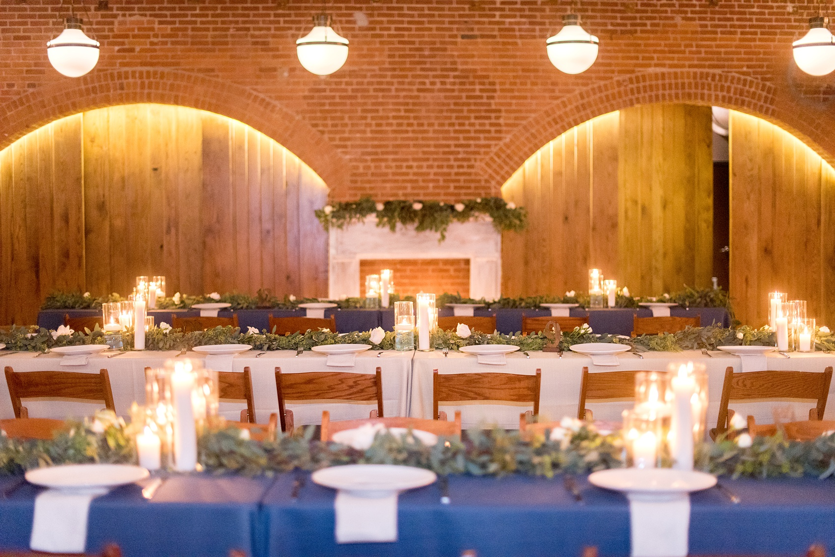 Durham wedding photos at The Cookery by Mikkel Paige Photography in North Carolina. The reception room had rectangular tables with garland greenery and candlelight illuminating the room.