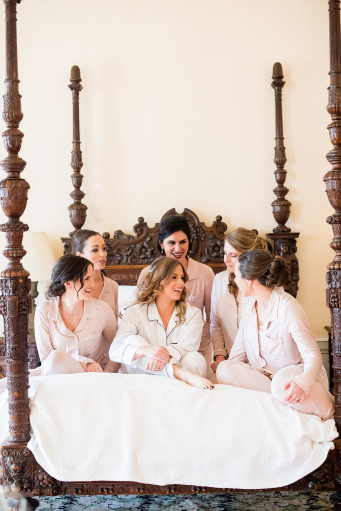 Wedding photos at Sleepy Hollow Country Club for a winter reception in January by Mikkel Paige Photography. Picture of the bride with her bridesmaids in pajamas before they got dressed for the day.