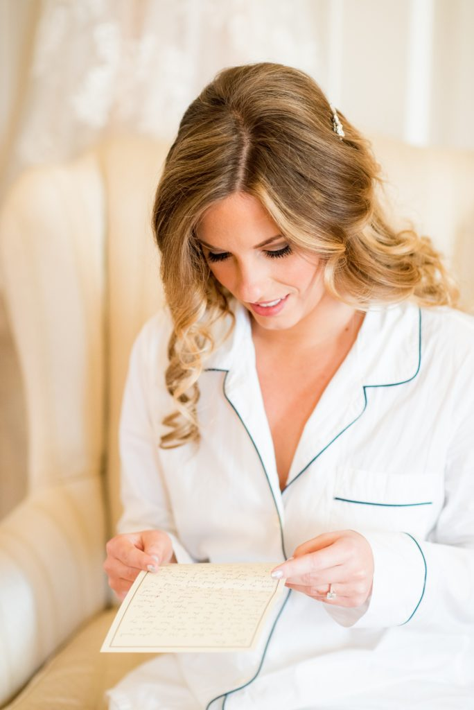 Wedding photos at Sleepy Hollow Country Club for a winter reception in January by Mikkel Paige Photography. The couple's Pittsburgh friends all contributed to a cookie table as dessert for the reception. Picture of the bride in white pajamas reading a letter from the groom.