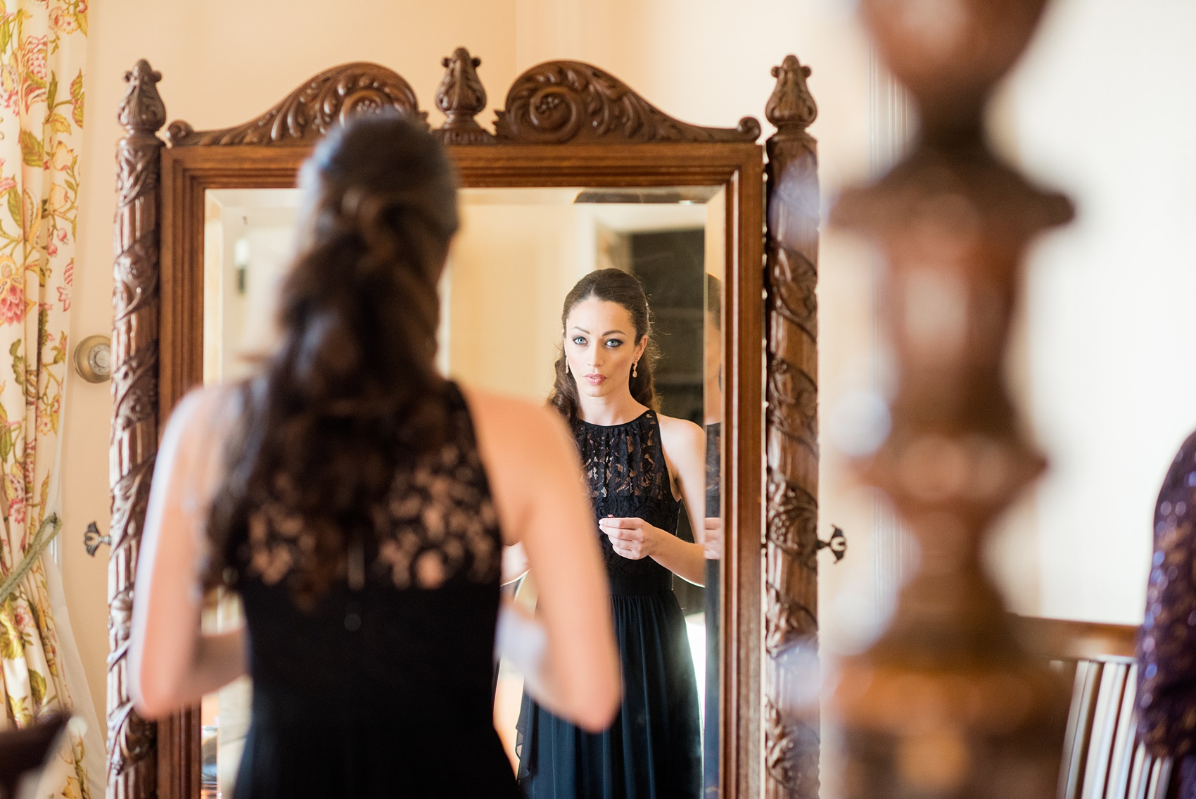 Wedding photos at Sleepy Hollow Country Club for a winter reception in January by Mikkel Paige Photography. The maid of honor looked in the mirror during getting ready pictures in her black lace gown.