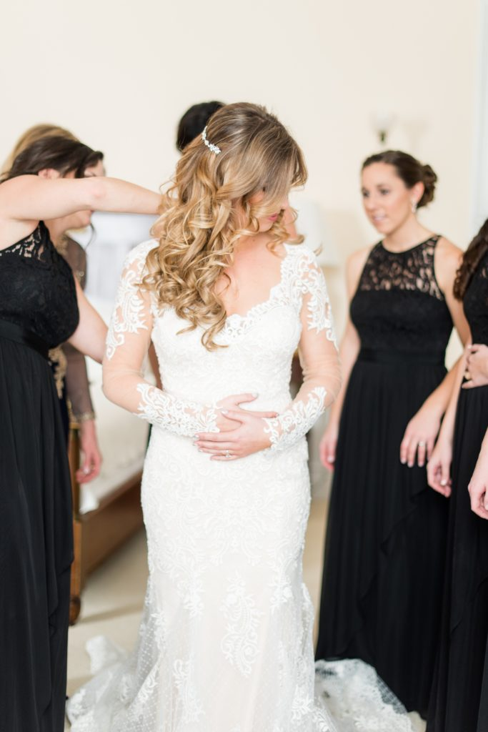 Wedding photos at Sleepy Hollow Country Club for a winter reception in January by Mikkel Paige Photography. The mother of the bride helped her daughter close the buttons of her lace dress on her winter wedding day.