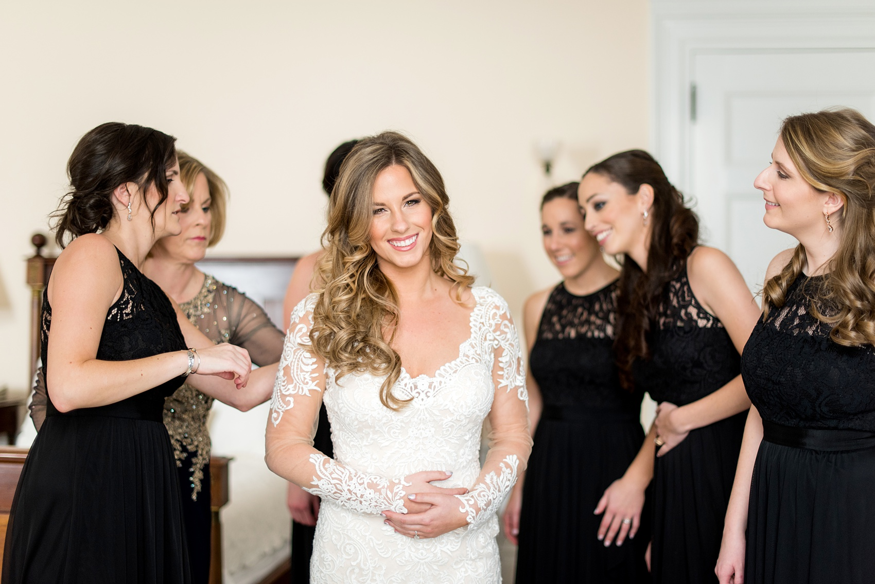 Wedding photos at Sleepy Hollow Country Club for a winter reception in January by Mikkel Paige Photography. The bridesmaids helped the bride dress in her lace gown on her winter wedding day.