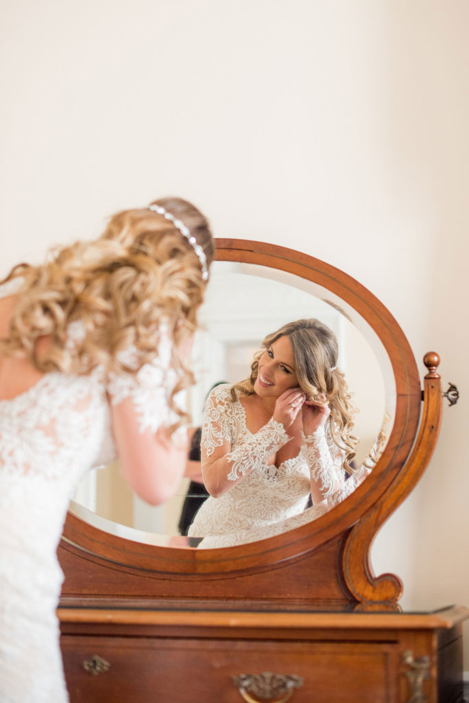 Wedding photos at Sleepy Hollow Country Club for a winter reception in January by Mikkel Paige Photography. A picture of the bride looking into the mirror to put on her vintage diamond and pearl earrings.