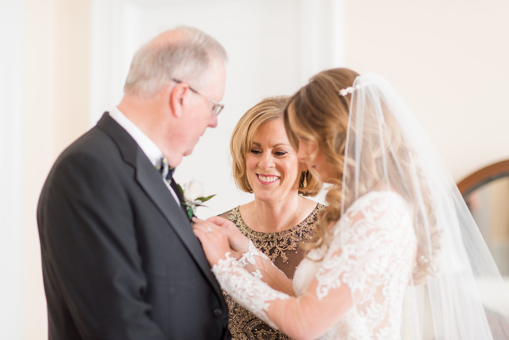 Wedding photos at Sleepy Hollow Country Club for a winter reception in January by Mikkel Paige Photography. A picture of the bride helping pin on her father's boutonniere.
