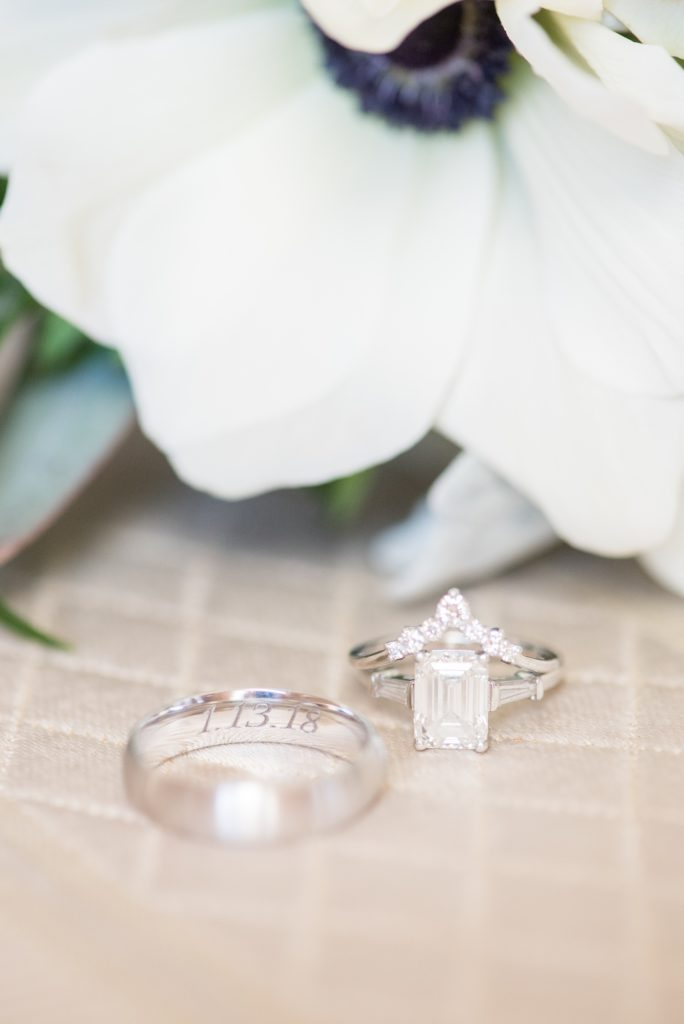 Wedding photos at Sleepy Hollow Country Club for a winter reception in January by Mikkel Paige Photography. A detail picture of their white gold wedding bands with their winter wedding date inscribed. The bride had an emerald cut diamond engagement ring and pointed band.