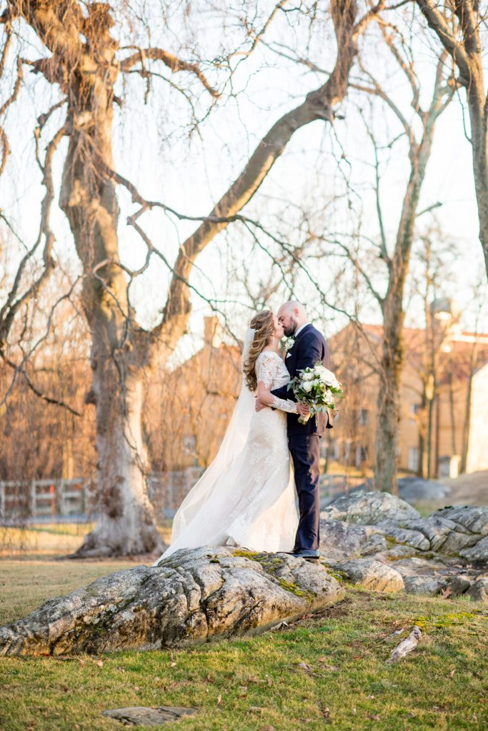 Wedding photos at Sleepy Hollow Country Club for a winter reception in January by Mikkel Paige Photography. A picture of the bride and groom kissing on rustic rocks during their winter wedding in New York.