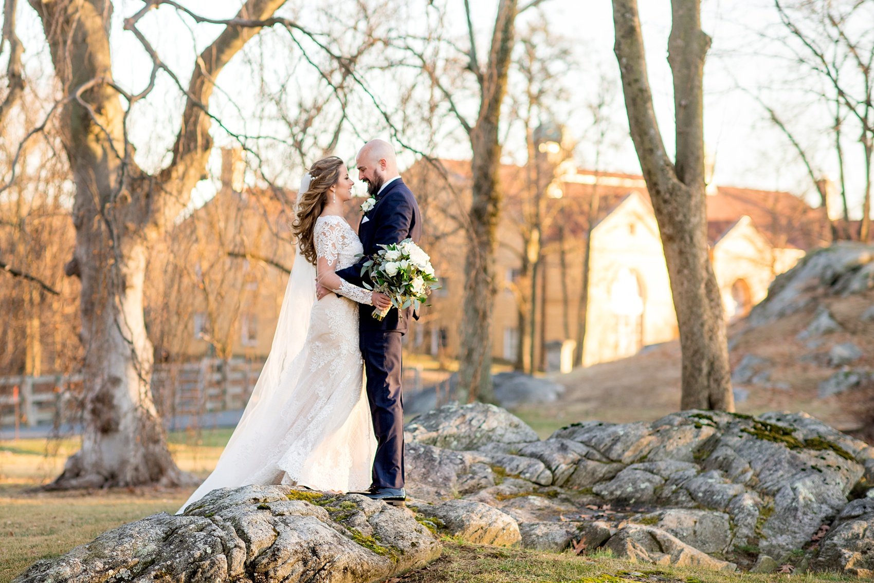 Wedding photos at Sleepy Hollow Country Club for a winter reception in January by Mikkel Paige Photography. A picture of the bride in her long sleeve, lace gown and groom in his navy blue tuxedo, looking at each other during their portraits.