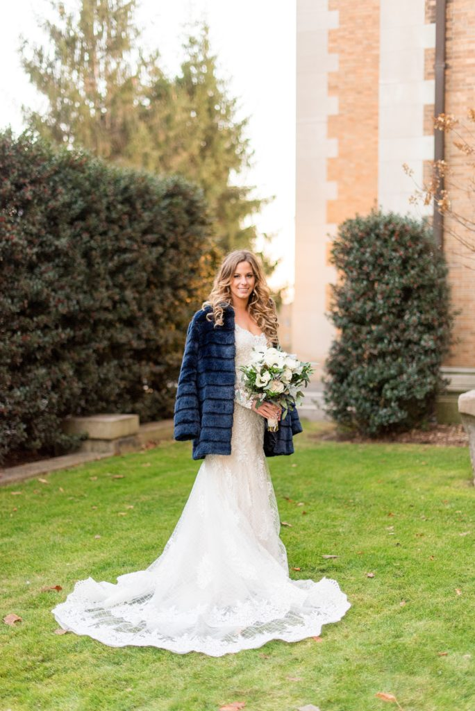 Wedding photos at Sleepy Hollow Country Club for a winter reception in January by Mikkel Paige Photography. The bride wore a long sleeve, lace gown with an open back and a blue faux fur coat for her winter wedding.