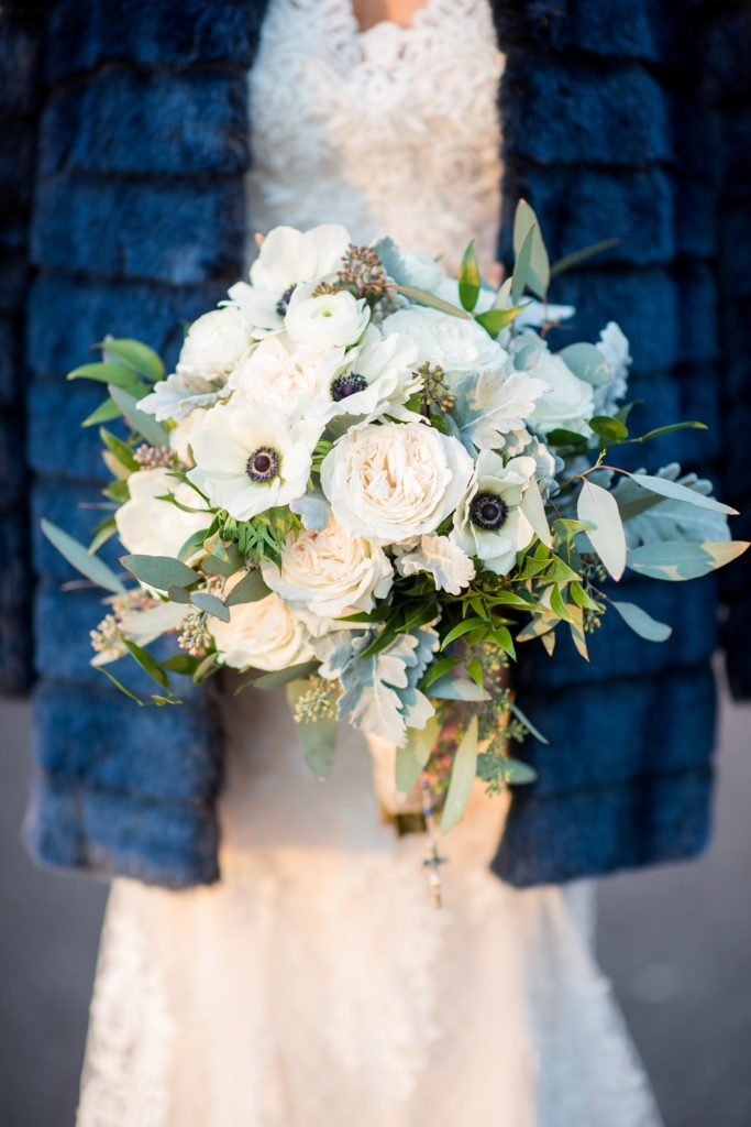 Wedding photos at Sleepy Hollow Country Club for a winter reception in January by Mikkel Paige Photography. A detail picture of the bride's winter bouquet, with white and green flowers, including anemones, eucalyptus and roses against her blue fur coat.
