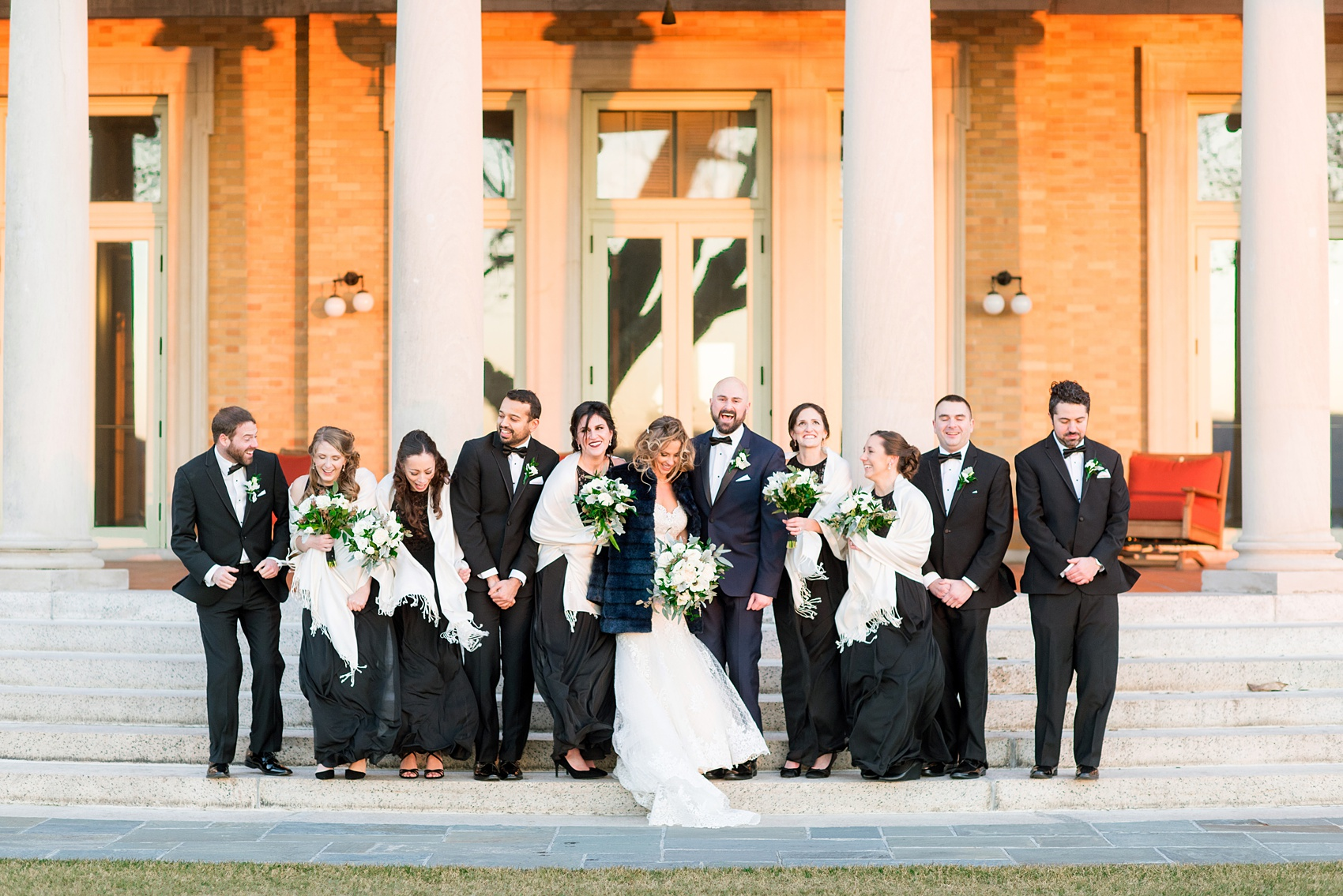 Wedding photos at Sleepy Hollow Country Club for a winter reception in January by Mikkel Paige Photography. The bridal party is pictured with white shawls, black lace gowns, and black tuxedos on the iconic stairs with columns of this New York venue.
