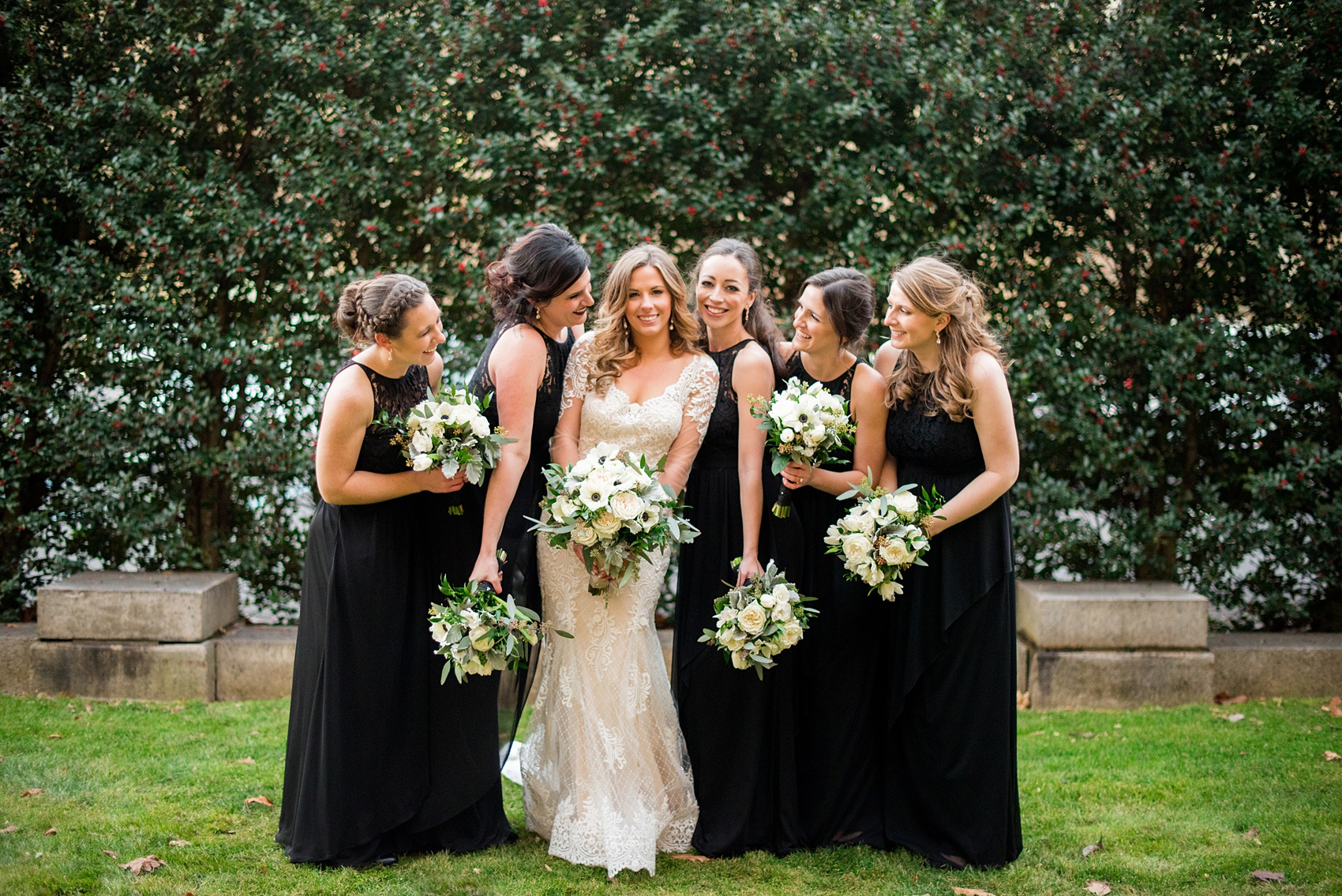 Wedding photos at Sleepy Hollow Country Club for a winter reception in January by Mikkel Paige Photography. The bridal party is pictured with white shawls and black lace gowns, surrounding the bride for her winter wedding.