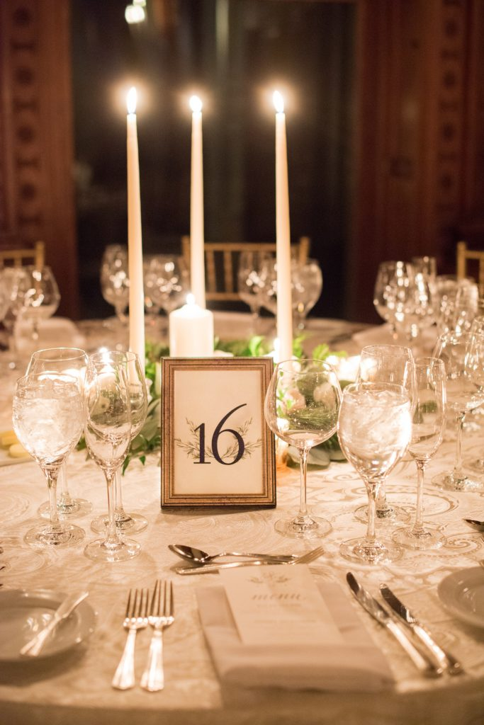 Wedding photos at Sleepy Hollow Country Club for a winter reception in January by Mikkel Paige Photography. Their New York winter wedding venue was decorated with a lot of candlelight and custom signage, including their table numbers.