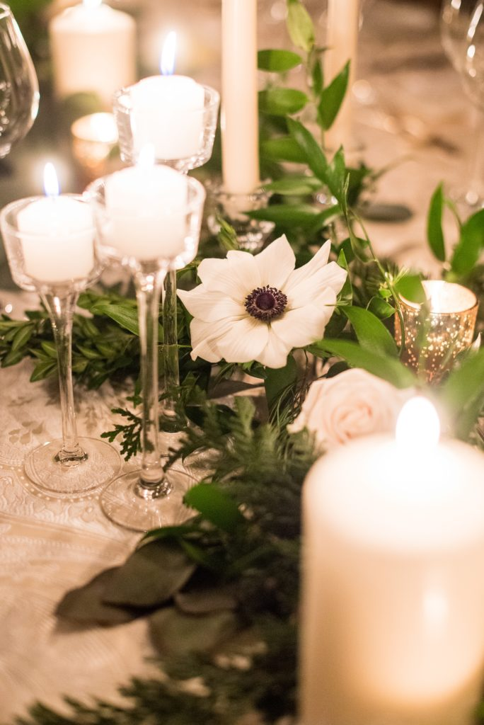 Wedding photos at Sleepy Hollow Country Club for a winter reception in January by Mikkel Paige Photography. Their New York winter wedding venue was drenched in greenery and warm candlelight.
