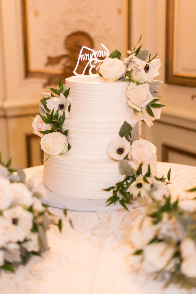 Wedding photos at Sleepy Hollow Country Club for a winter reception in January by Mikkel Paige Photography. Their tiered white wedding cake was covered with buttercream, a custom wine and beer topper and white and green flowers.