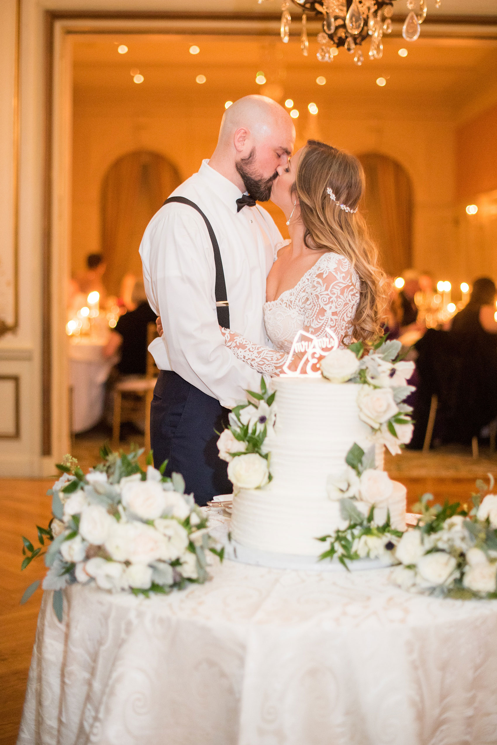 Wedding photos at Sleepy Hollow Country Club for a winter reception in January by Mikkel Paige Photography. The couple's Pittsburgh friends all contributed to a cookie table as dessert for the reception. The bride and groom kissed in front of their wedding cake before the cutting.