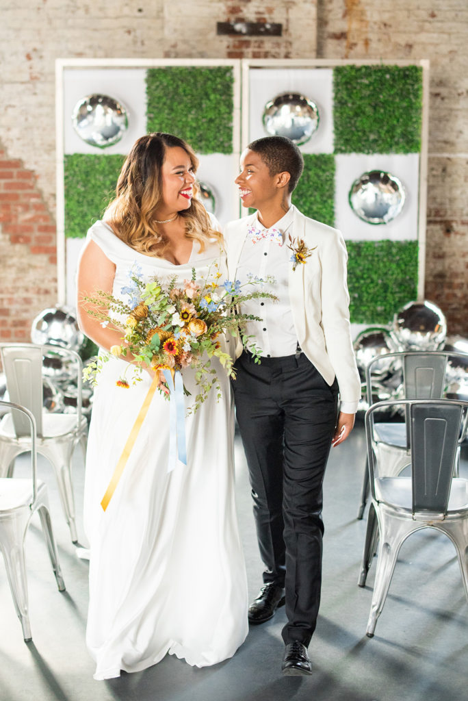 Mikkel Paige Photography photos of a wedding at the Green Building in Brooklyn, New York. This same sex, gay marriage styled shoot was created by Color Pop Events. They recited vows during their ceremony in front of silver mylar balloons and green square boxwood patches. The bride wore a white, silk cowl neck gown and the bride groom in a white coat with colorful bow tie.