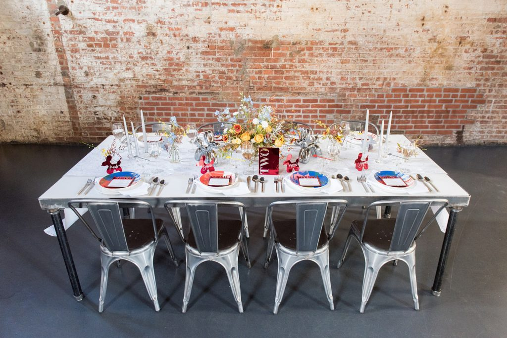 Mikkel Paige Photography photos of a wedding at the Green Building in Brooklyn, New York. This same sex, gay marriage styled shoot was created by Color Pop Events. The urban dinner table was styled by Taylor and Hov, inspired by Jeff Koons and neo pop art. Flower centerpieces are by Abby Tabak Studio.