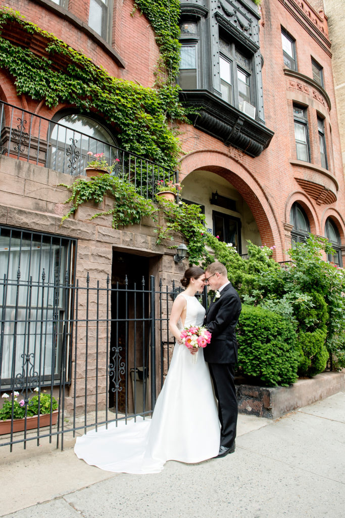 Manhattan Central Park wedding photos by Mikkel Paige Photography at Loeb Boathouse venue. These bride and groom pictures show a timeless couple having fun on their colorful day in this iconic NYC landmark and Upper West Side. The bride held a pink peony bouquet for their June celebration and wore a boat-neck gown with buttons down the back. A brownstone with creeping ivy completed the image. Click through for the complete post! #CentralParkWedding #CityWedding #brideandgroom