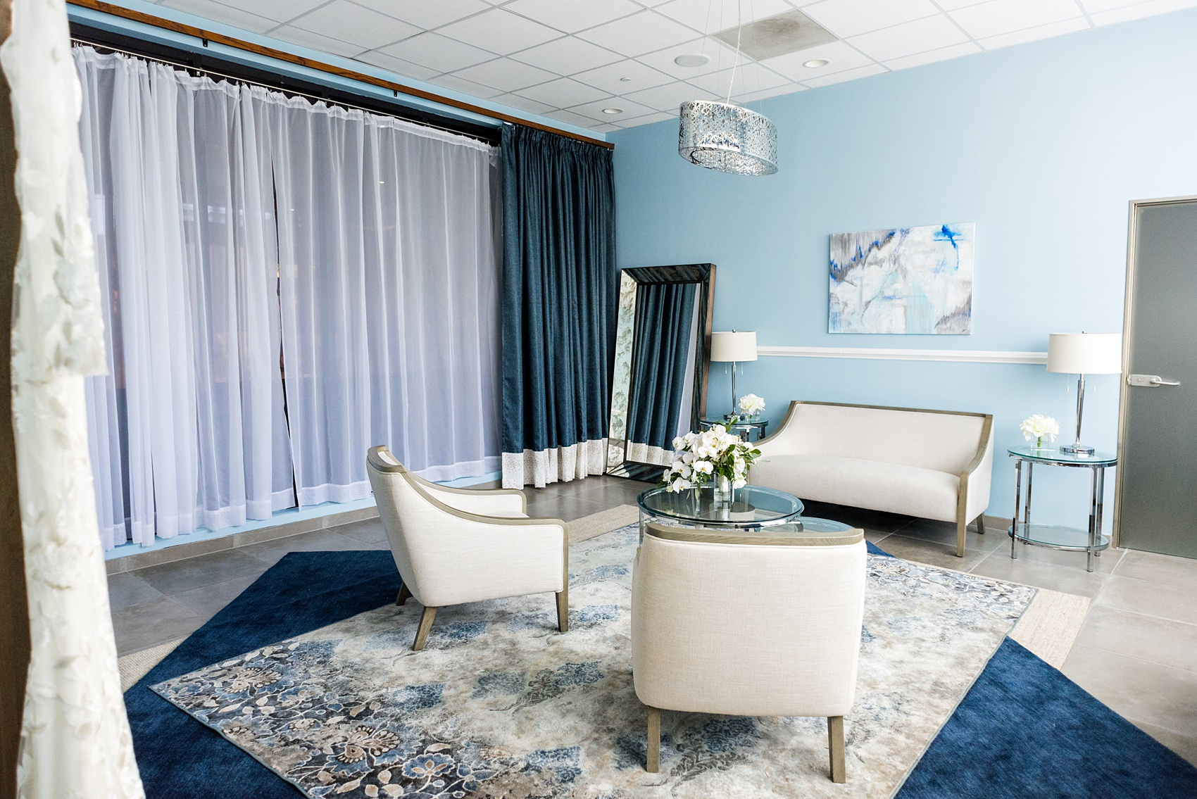 Downtown Raleigh wedding venue photos of Vidrio on Glenwood South, and their beautiful new bridal suite. Blue hues and neutral furniture are framed by paintings and a full length mirror in this beautiful space. #MikkelPaige #Vidrio #DowntownRaleigh #RaleighWeddingVenues