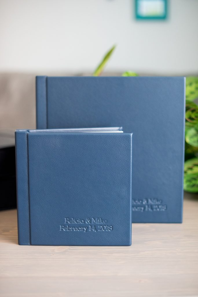 """Photos from a winter wedding at Central Park Loeb Boathouse in NYC, by Mikkel Paige Photography, are beautifully displayed. The bride and groom chose a navy blue leather 12x12"""" album with spine and cover debossing to remember their day. #mikkelpaige #centralparkwedding #loebboathousewedding #NYCweddingphotographer #navyblueweddingalbum #parentalbums"""
