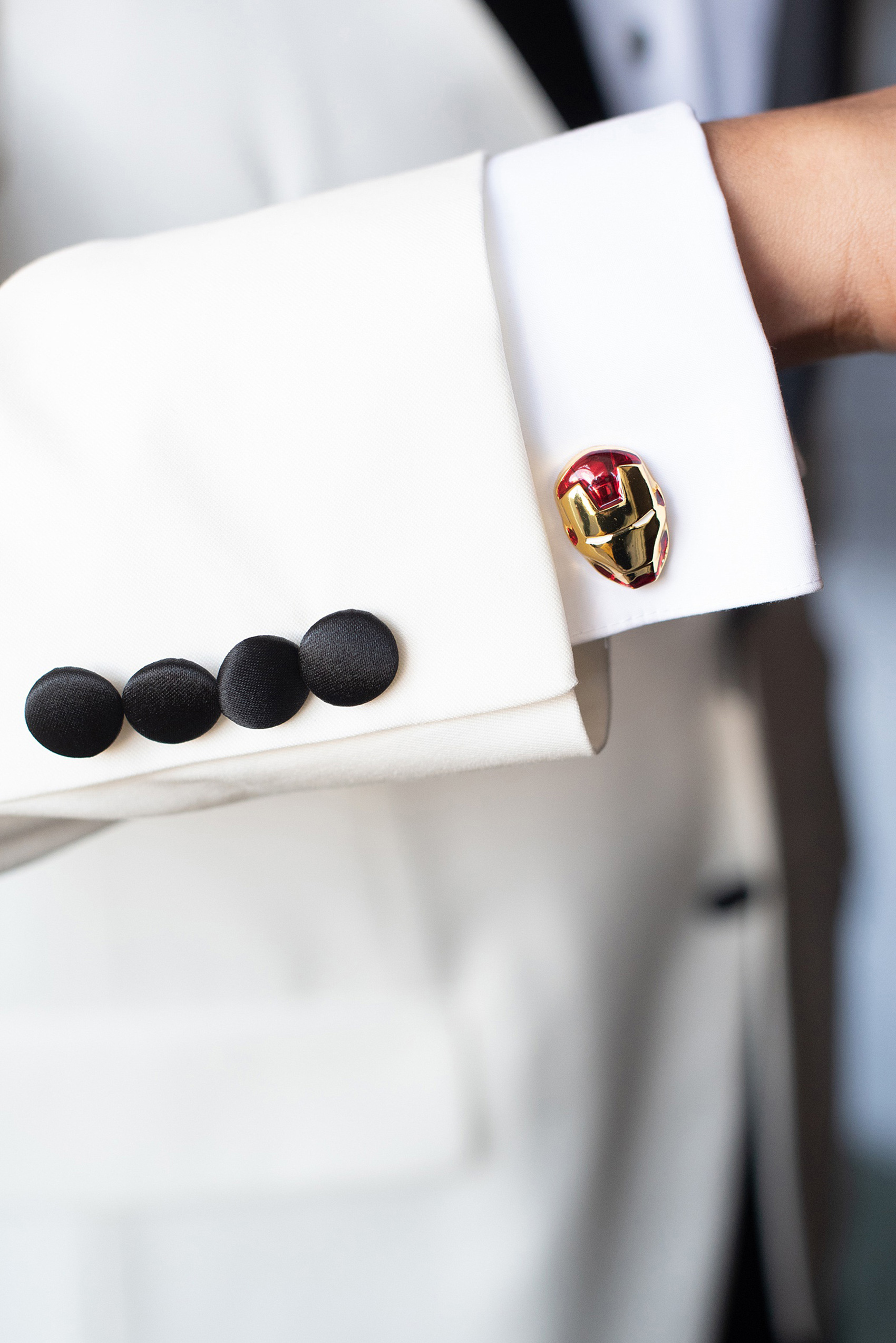Photographs of a Walt Disney World groom by Mikkel Paige Photography. As a lover of Marvel comics, he wove a small detail from Iron Man into his white tuxedo with gold and red cufflinks. He got ready for his day at the dream resort, the Grand Floridian, with his groomsmen and wore a red rose boutonniere for his bride's love of a Beauty and the Beast theme. #disneywedding #disneybride #waltdisneyworld #DisneyWorldWedding