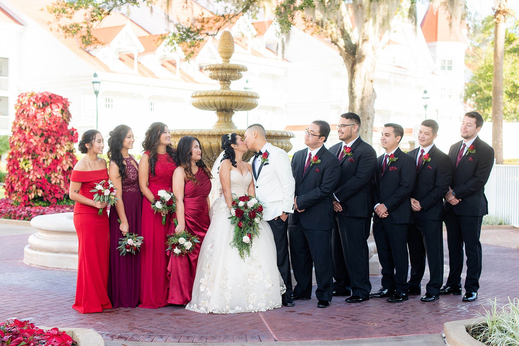 Photographs of a Walt Disney World bridal party by Mikkel Paige Photography. The bride chose the venues of the Grand Floridian, Wedding Pavilion and The Contemporary Resort for photos and fun locations. One even overlooked the Magic Kingdom Park! Their dream wedding included red details: the bridesmaids wore mismatched dresses and carried rose bouquets. #disneywedding #disneybride #waltdisneyworld #DisneyWorldWedding #BeautyandtheBeast #redrosewedding