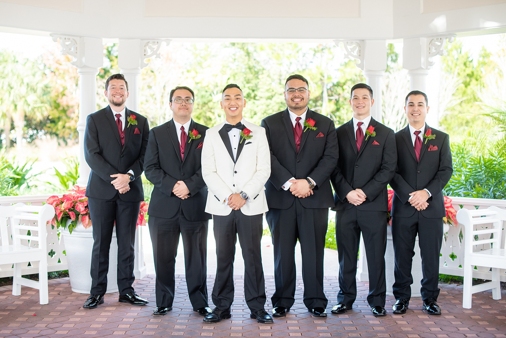 Photographs of a Walt Disney World bridal party by Mikkel Paige Photography. The groom wore a white tuxedo to his wedding venues of the Grand Floridian, Wedding Pavilion and The Contemporary Resort. They all wore rose boutonnieres and marvel comic cufflinks, a small detail that was an awesome way to incorporate a fun idea. #disneywedding #disneybride #waltdisneyworld #DisneyWorldWedding #BeautyandtheBeast #redrosewedding