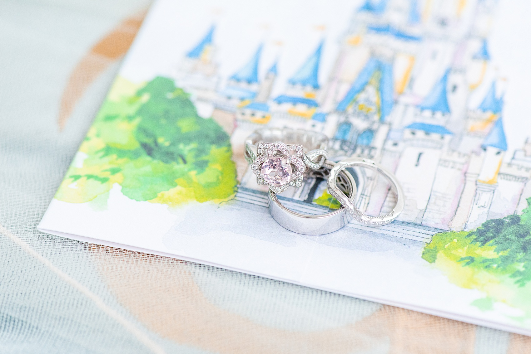 Photographs of a Walt Disney World wedding by Mikkel Paige Photography. The bride's engagement ring was themed to Beauty and the Beast with a pink morganite center stone. It perfectly matched their invitations with Cinderella Castle as the main watercolor and the movie glass rose dome on the RSVP card. #disneywedding #disneybride #waltdisneyworld #DisneyWorldWedding #morganitering #pinkengagementring #rosering #BeautyandtheBeast