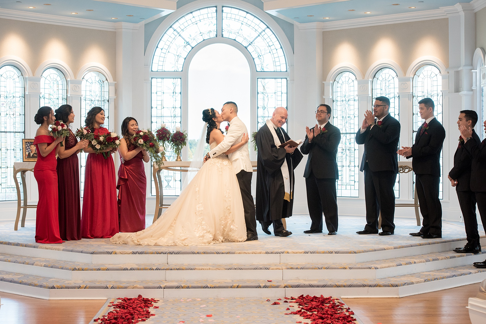 Photographs of a Walt Disney World wedding by Mikkel Paige Photography will give you ideas for a tasteful Beauty and the Beast theme. There was a glass dome with a red rose inside at the start of the ceremony with red rose petals scattered down the aisle for a small, intimate guest list at the Wedding Pavilion next to the Grand Floridian resort. #disneywedding #disneybride #waltdisneyworld #DisneyWorldWedding #DisneyCeremony #DisneyWorldWeddingPavilion