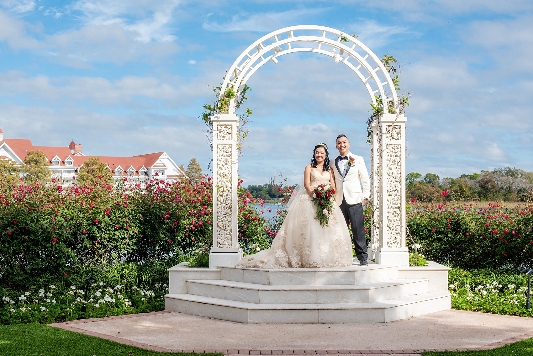 Walt Disney World photographs by Mikkel Paige Photography. The bride and groom had December pictures at the Grand Floridian Resort, Wedding Pavilion and Contemporary Hotel. It had a Beauty and the Beast theme and the bride wore a beautiful rose embroidered dress, befitting of a princess. Her red rose bouquet had holiday greenery and a cascading effect. The groom wore a white tuxedo. #disneywedding #disneybride #waltdisneyworld #DisneyWorldWedding #cascadingbouquet