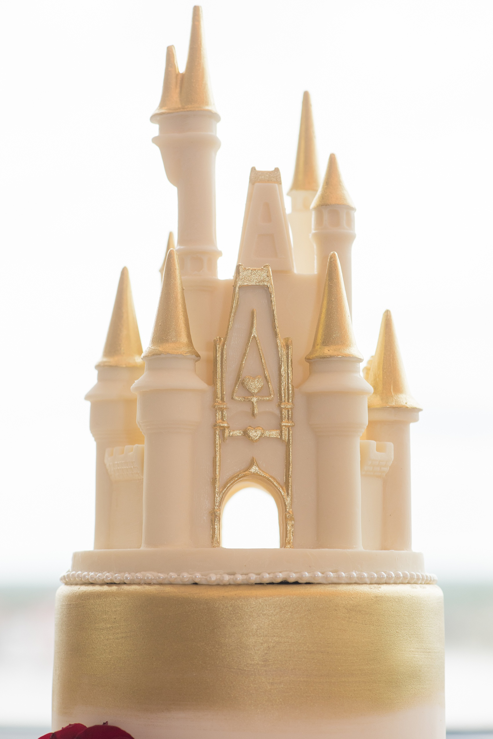 Photographs of a Walt Disney World wedding by Mikkel Paige Photography will give you ideas for a tasteful theme. The bride and groom's cake had red fondant with a Marvel Iron Man emblem. The top had a white chocolate Cinderella Castle with a brush of gold for a small reception celebration. #disneywedding #DisneyCake #DisneyWorldWedding #Disneyreception #californiagrill #ContemporaryResort #disneyweddingcake #MarvelWeddingCake #CinderellaCastleCake